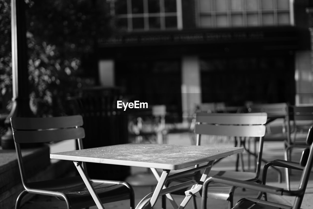chair, table, empty, outdoor cafe, absence, furniture, restaurant, no people, focus on foreground, cafe, sidewalk cafe, place setting, seat, day, indoors, close-up