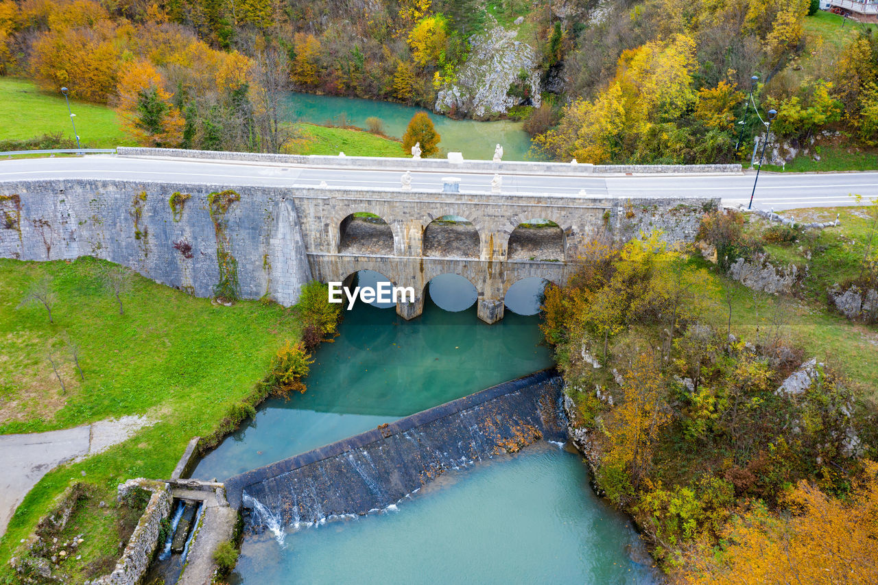 HIGH ANGLE VIEW OF BRIDGE OVER LAKE AGAINST TREES