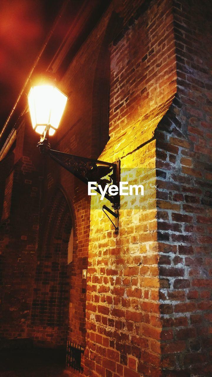 Low angle view of illuminated lantern mounted on brick wall