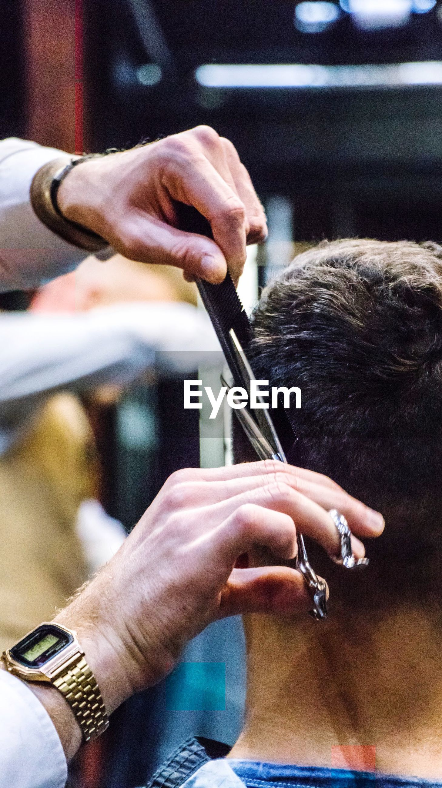 Cropped hands of barber cutting man hair in salon