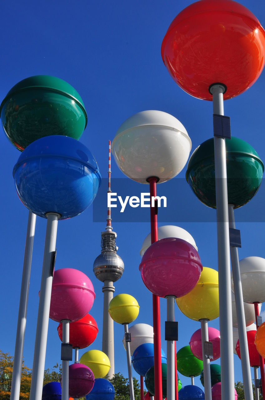 Low Angle View Of Colorful Lanterns And Fernsehturm Against Sky