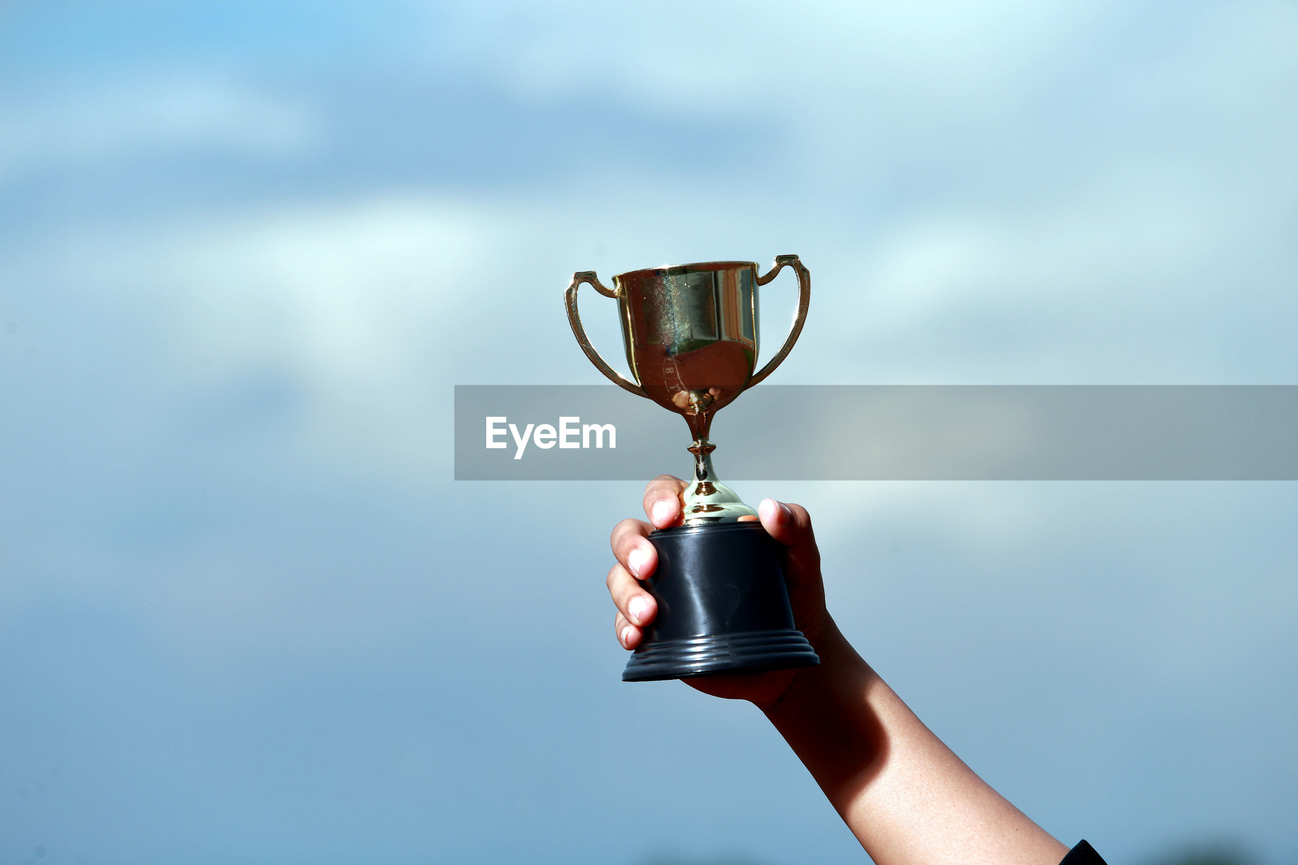 Cropped hand of woman holding trophy against sky