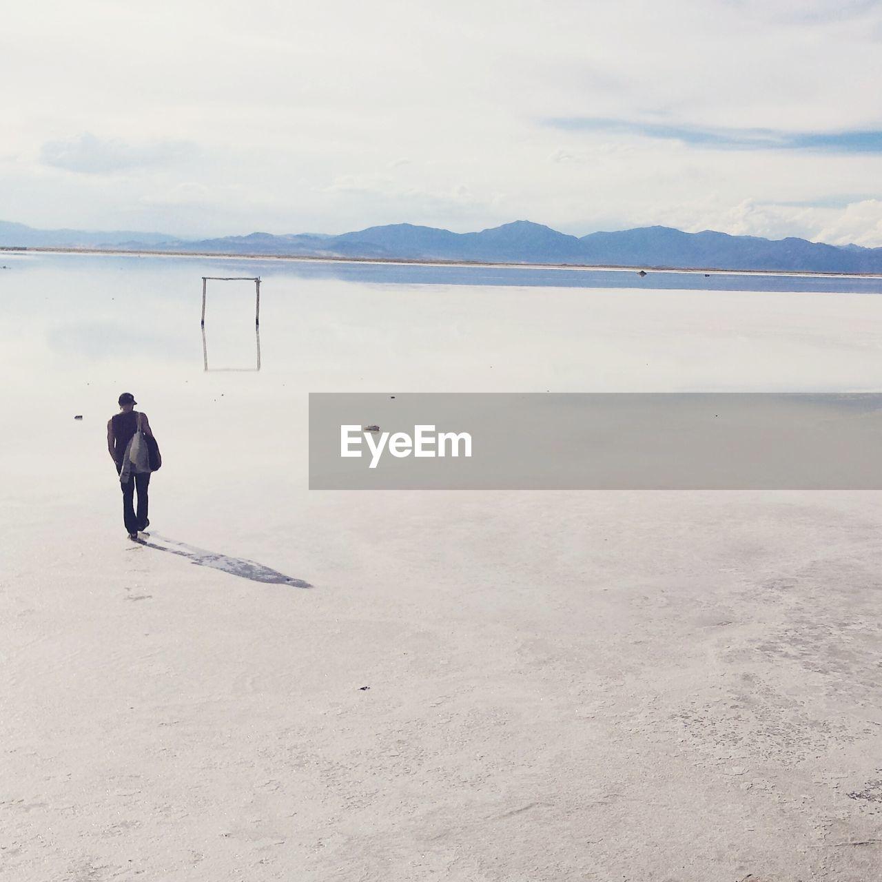 Full length rear view of man walking on salinas grandes against sky