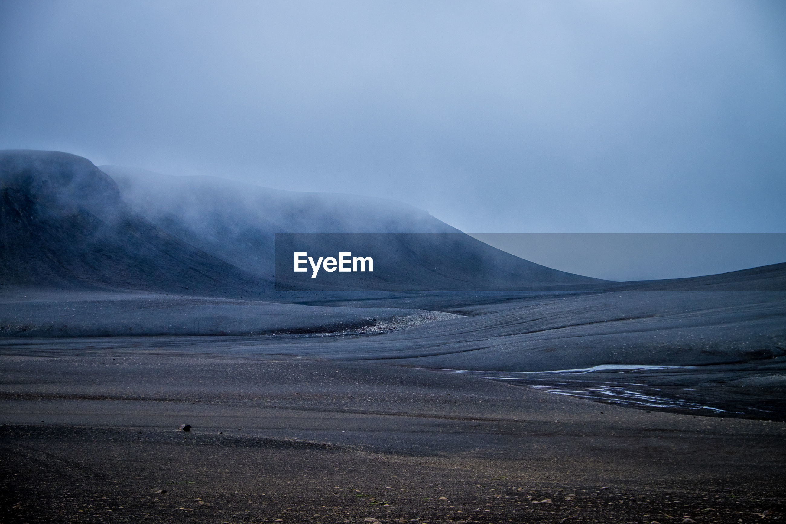 Scenic view of landscape and mountains against cloudy sky