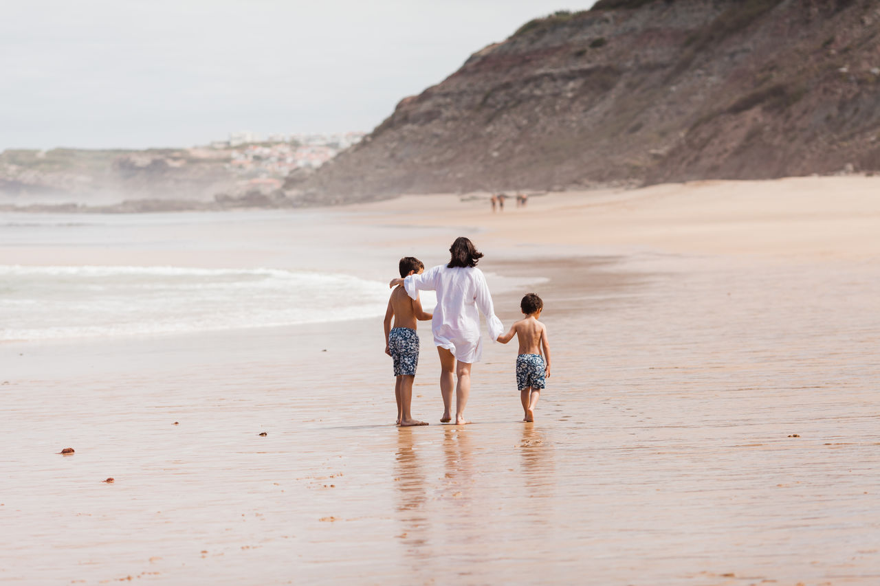 Siblings With Mother Walking At Beach Against Sky
