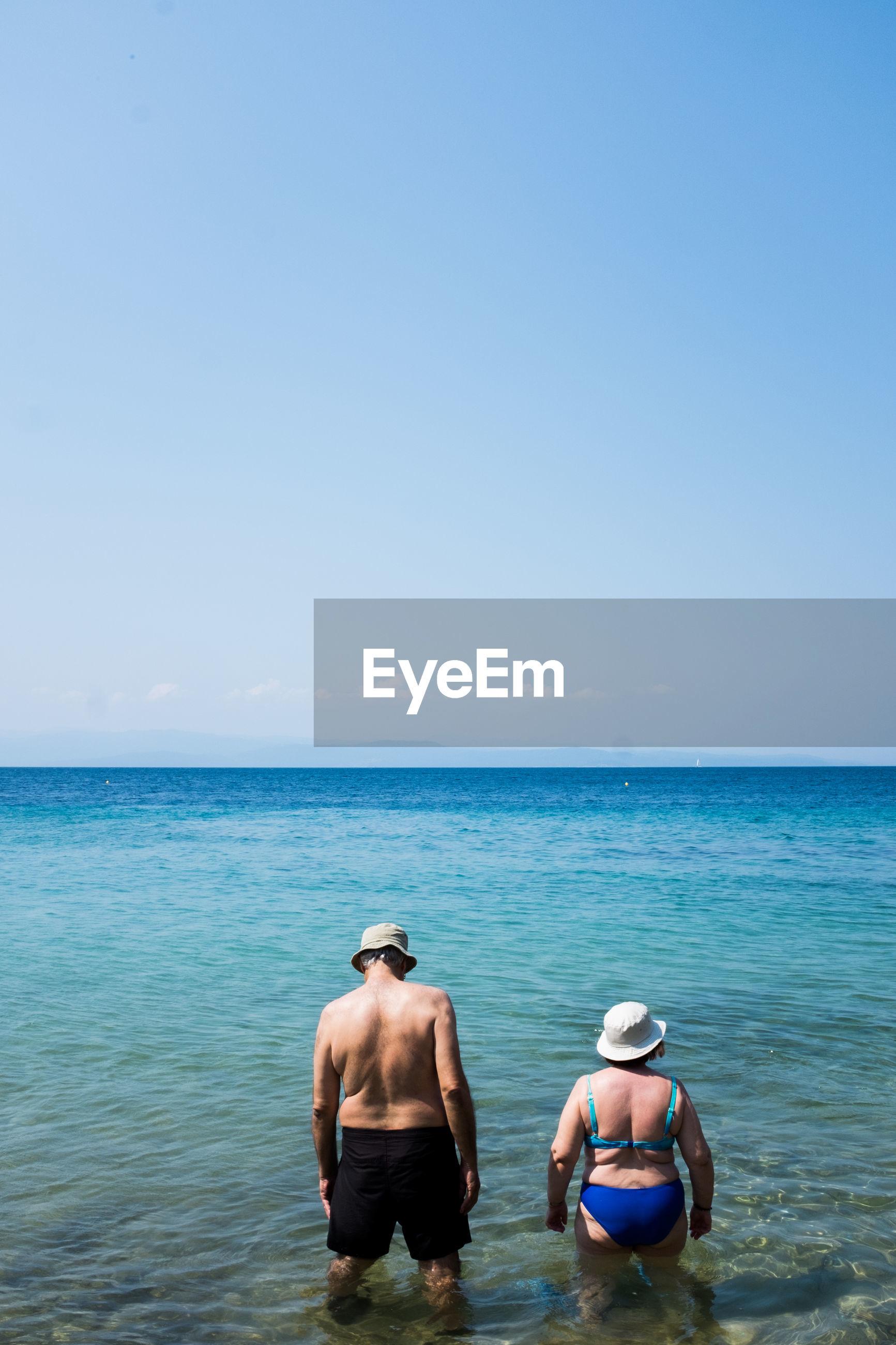 REAR VIEW OF MEN IN SEA AGAINST SKY