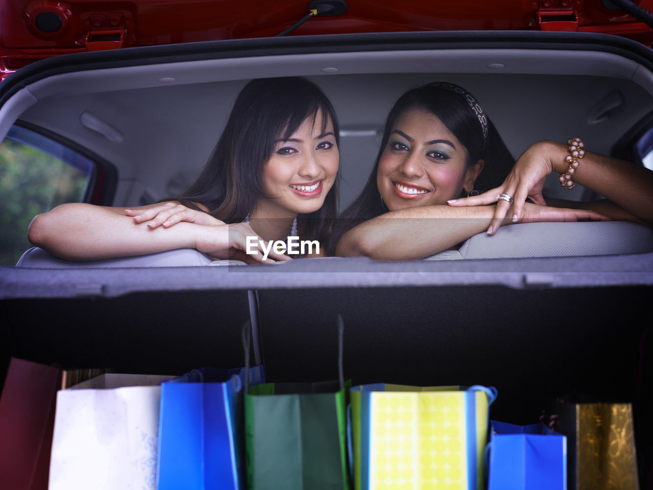 Portrait of cheerful female friends with shopping bags in car