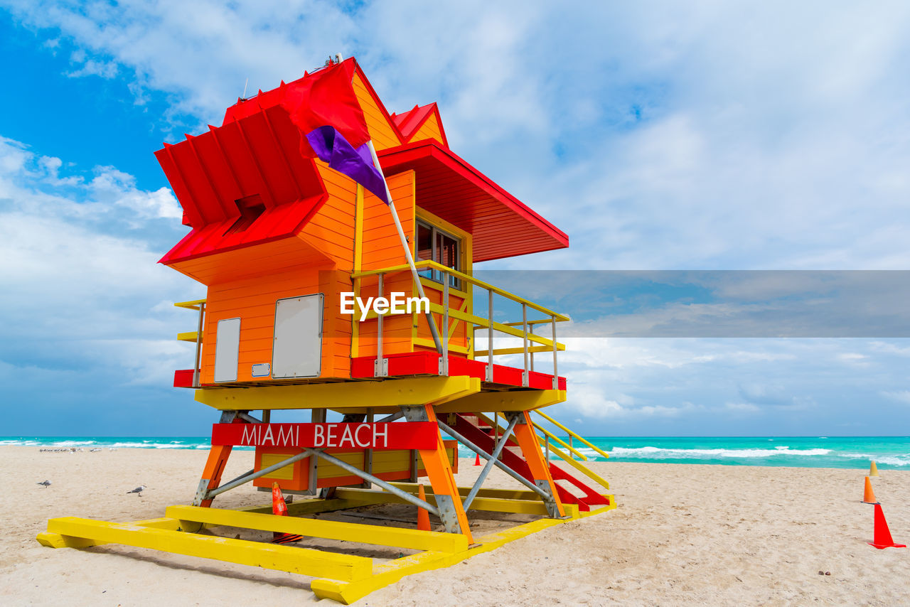 beach, land, cloud - sky, sea, water, sky, sand, hut, lifeguard hut, nature, man made structure, built structure, day, architecture, protection, red, security, beauty in nature, horizon over water, no people, outdoors