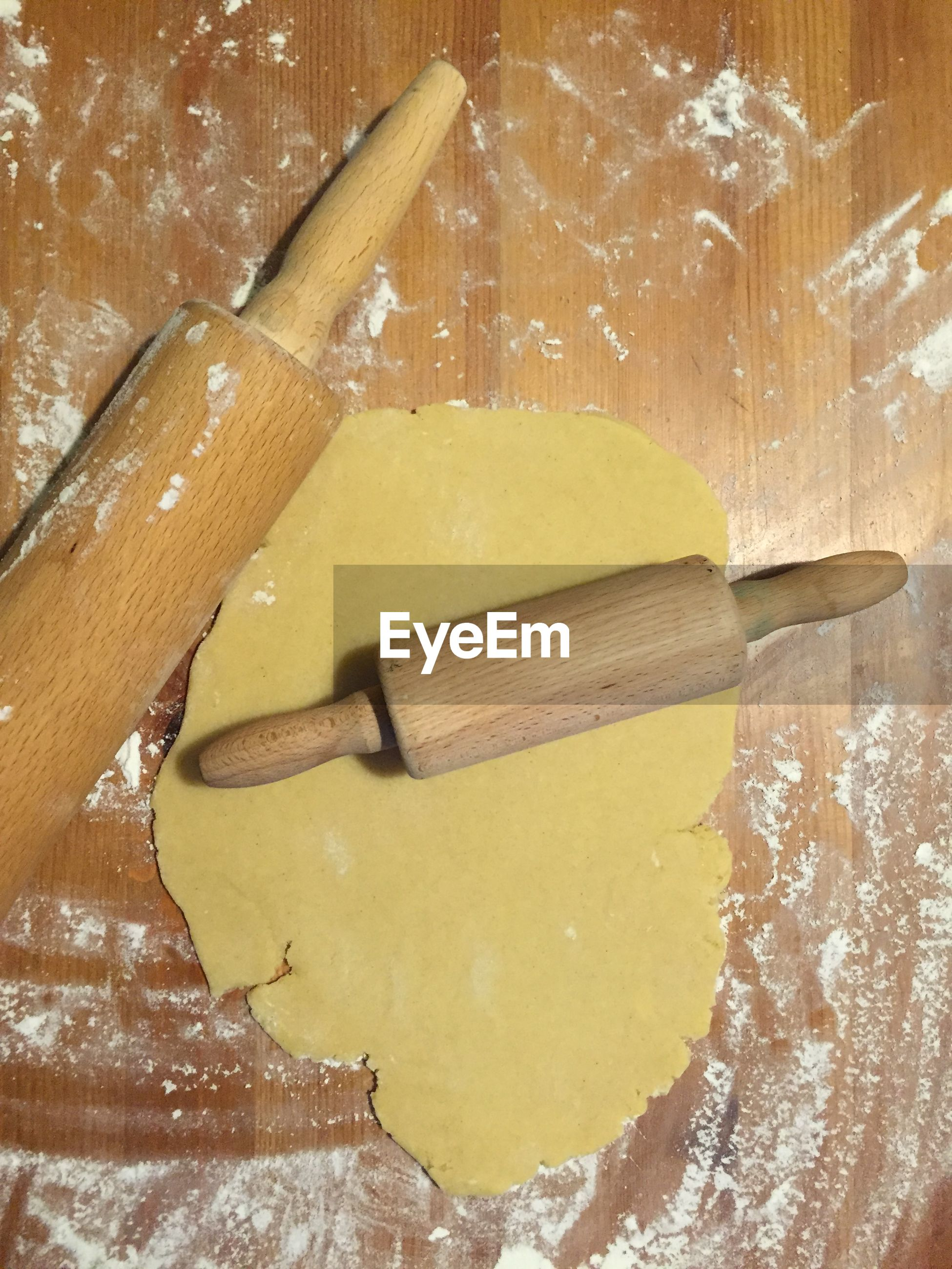 Directly above shot of rolling pins on cookie dough