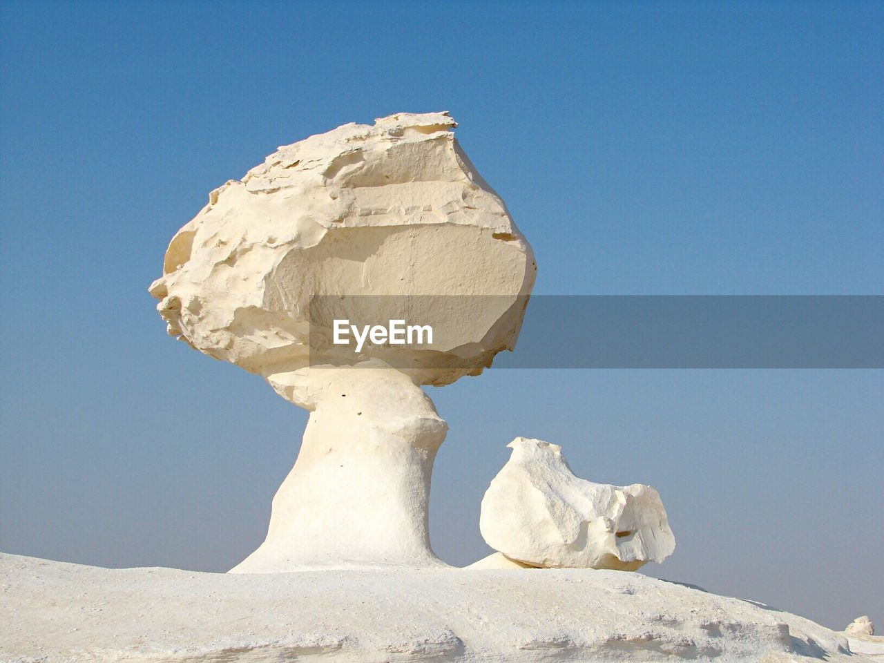 White rock formation in desert against clear blue sky