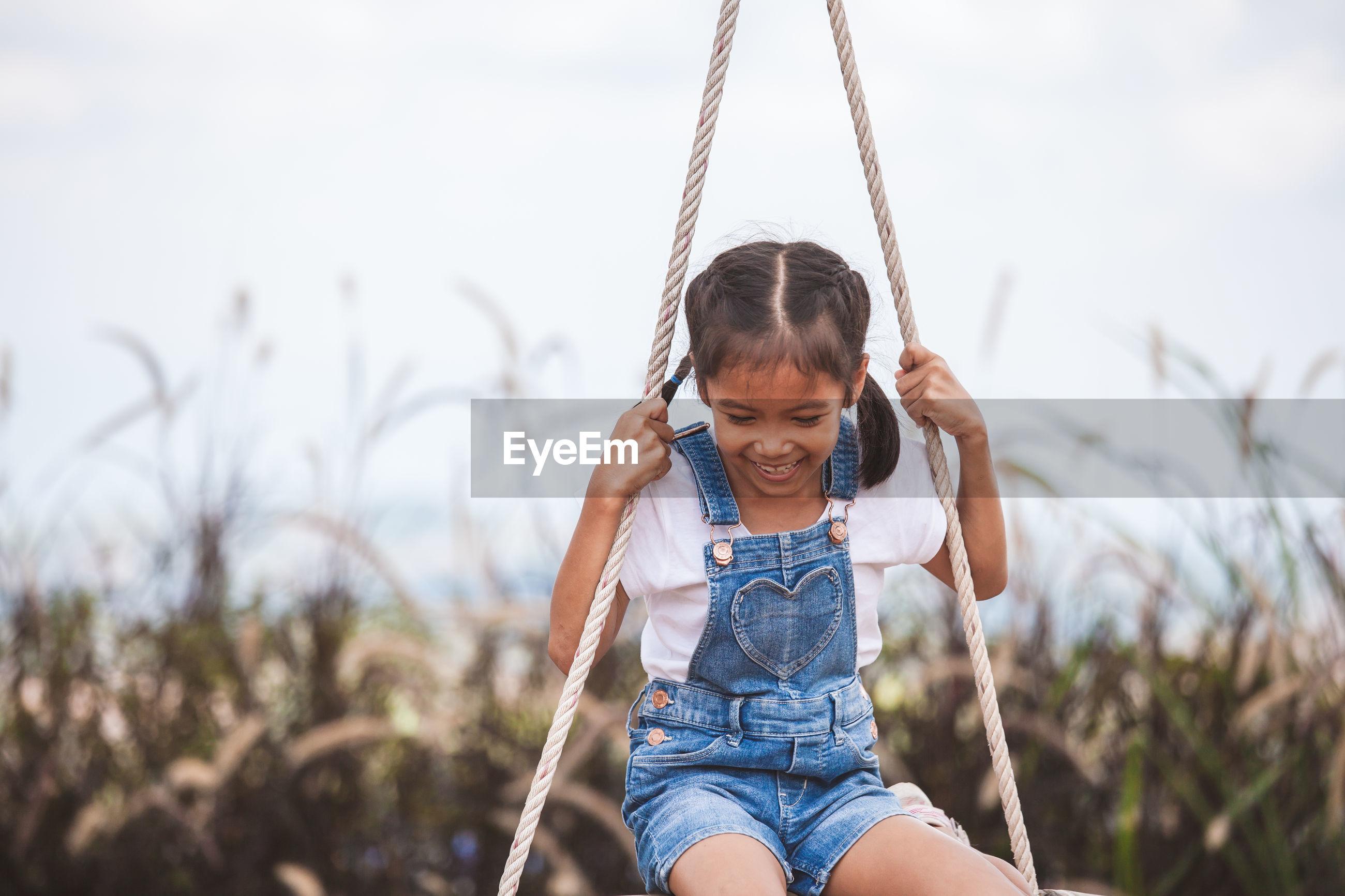 Cheerful girl swinging at playground