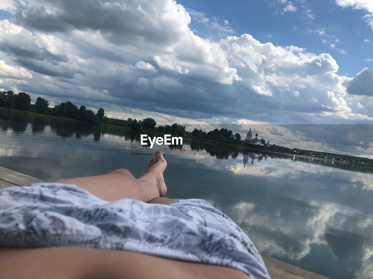 cloud - sky, sky, one person, water, human body part, low section, relaxation, body part, real people, human leg, leisure activity, nature, lifestyles, personal perspective, day, lake, tranquility, barefoot, human foot, outdoors, swimming pool