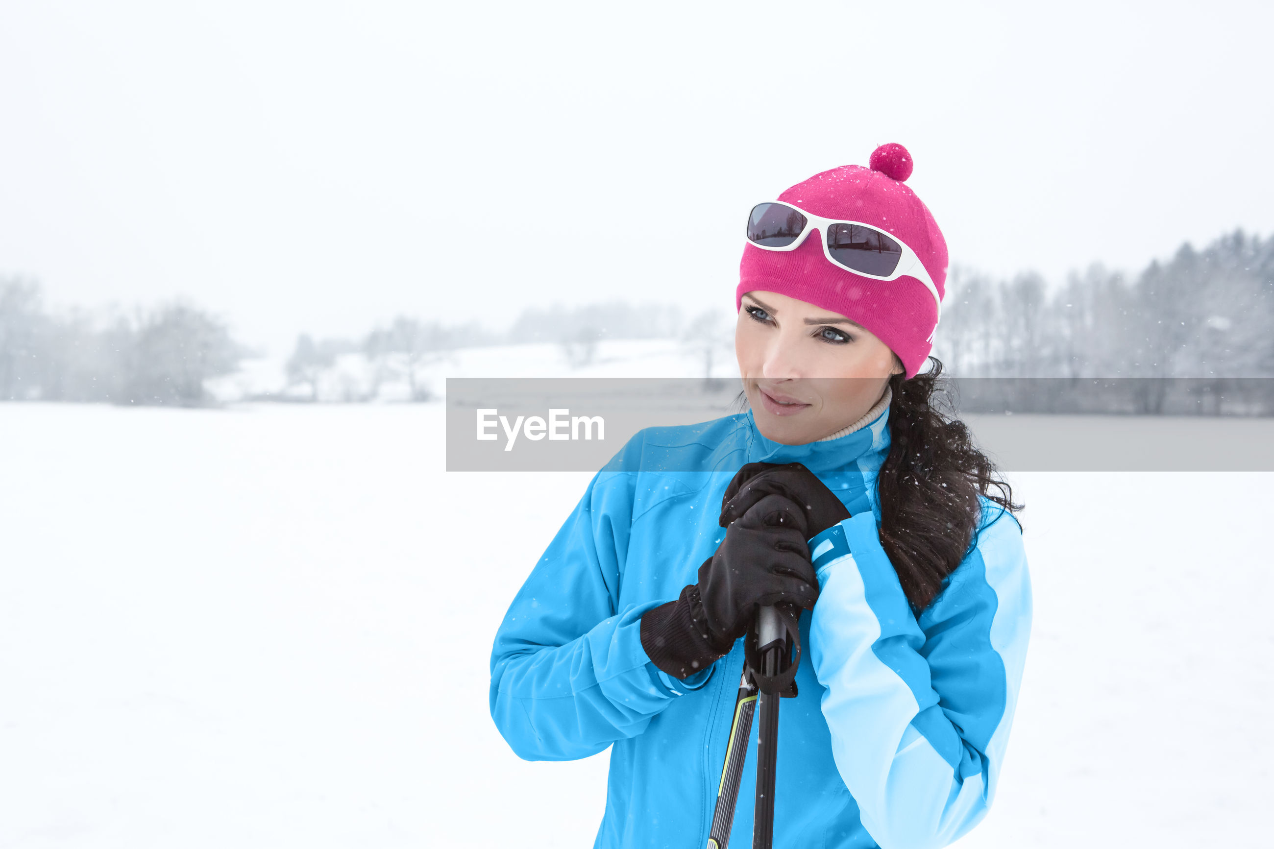 Thoughtful woman holding ski poles while standing on snow covered field