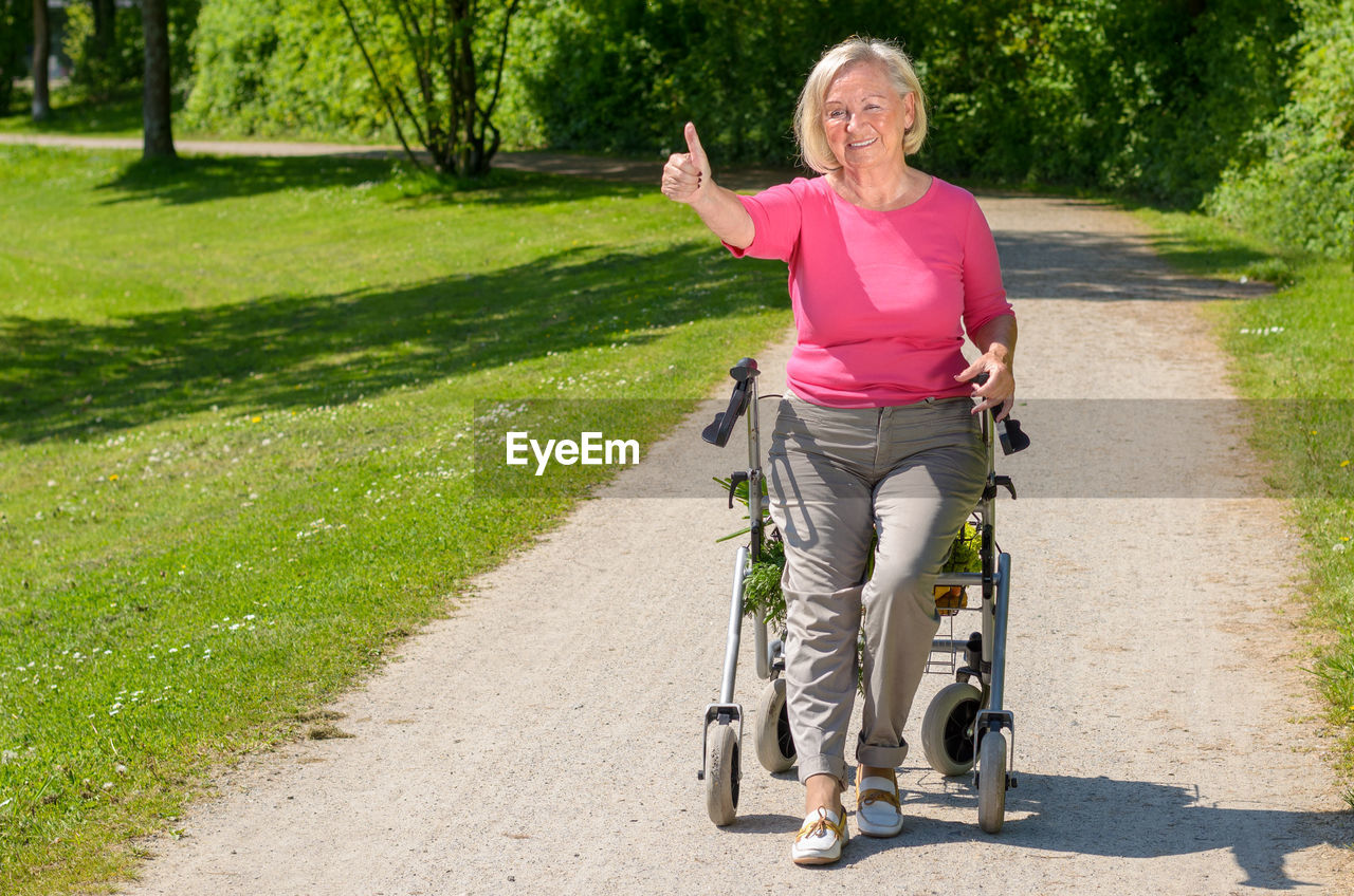 Disabled Senior Woman Showing Thumbs Up On Wheelchair On Road