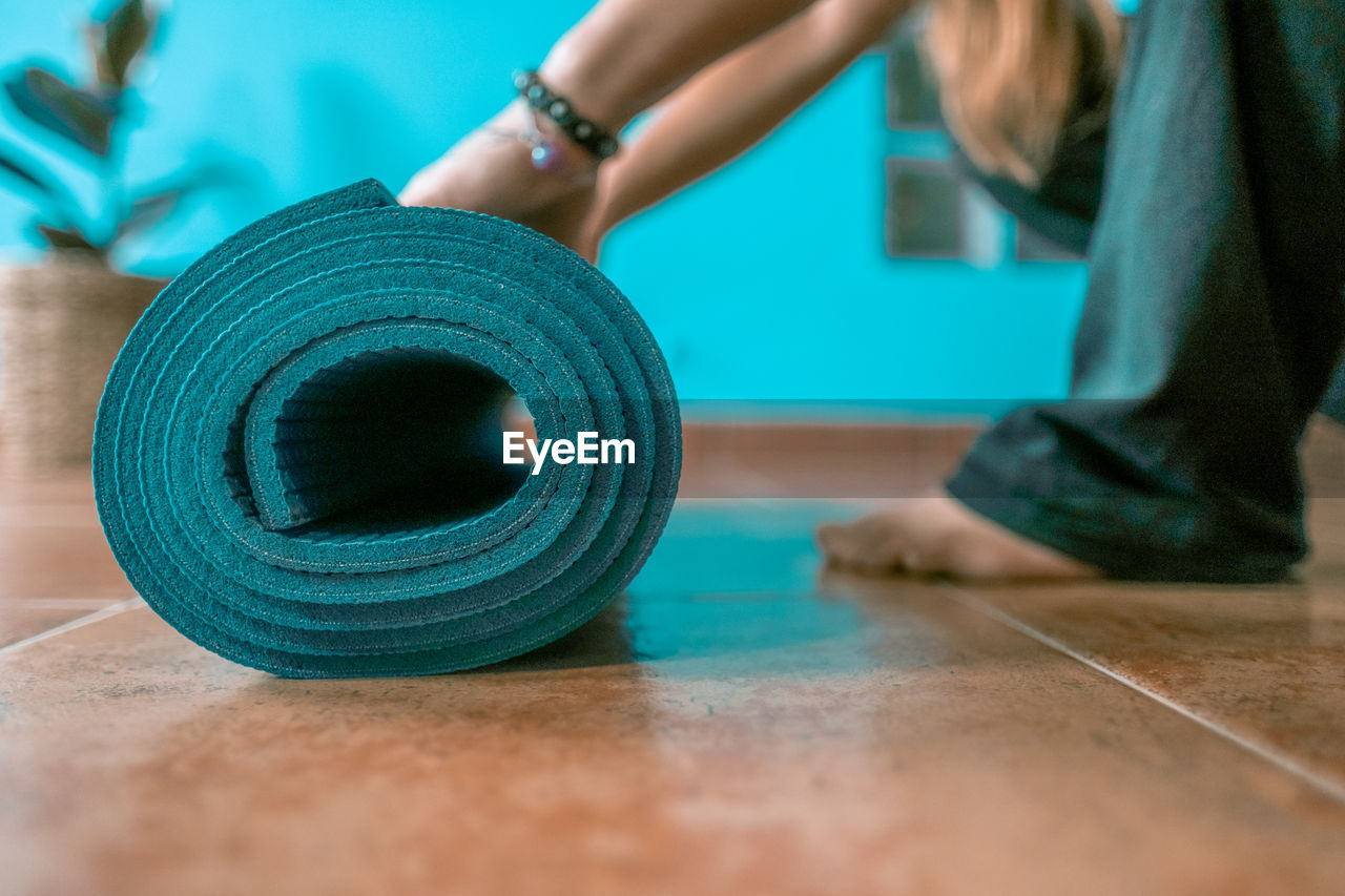 Low section of woman rolling up exercise mat at home