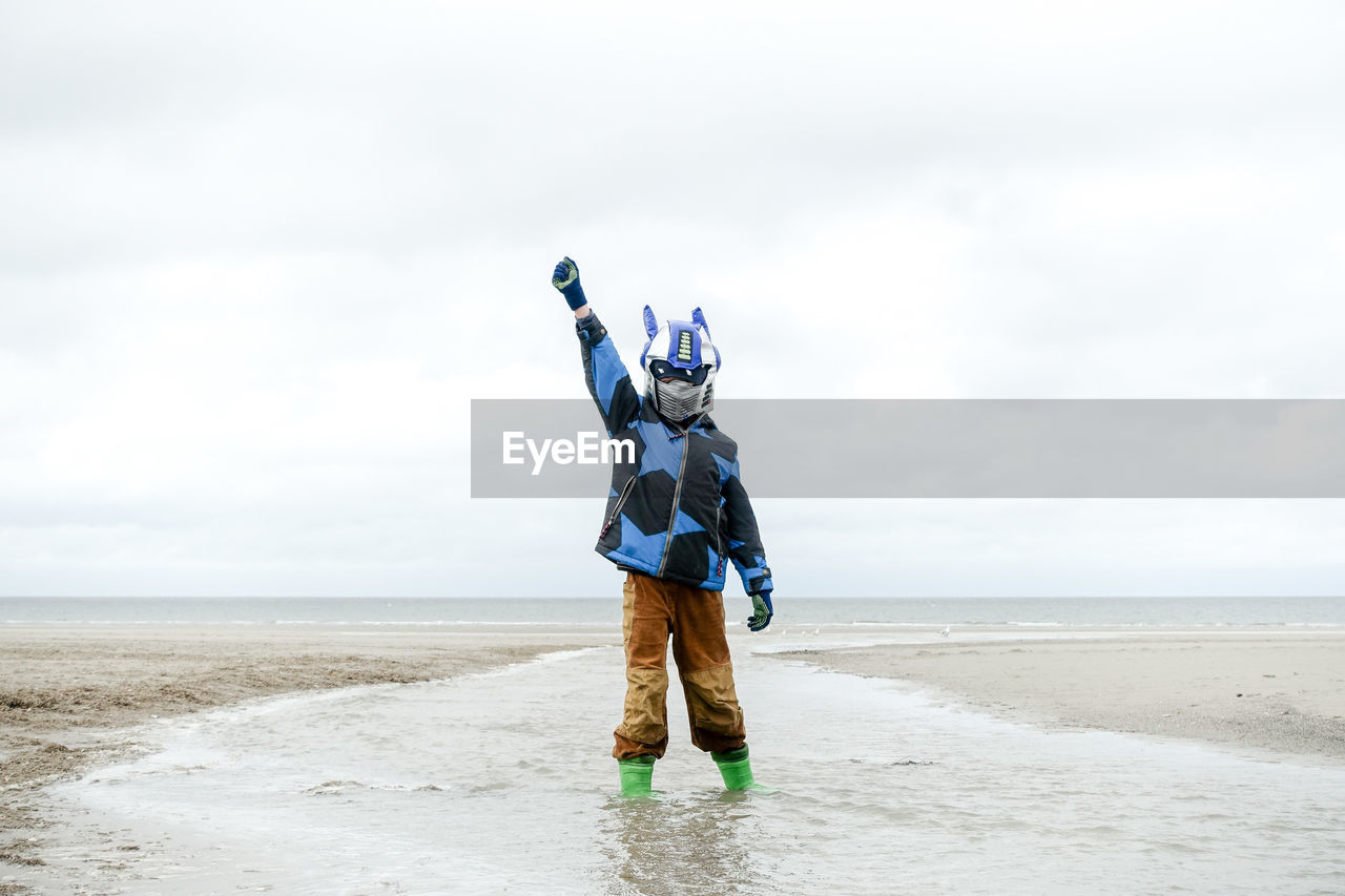 Full Length Of Disguised Boy On Beach