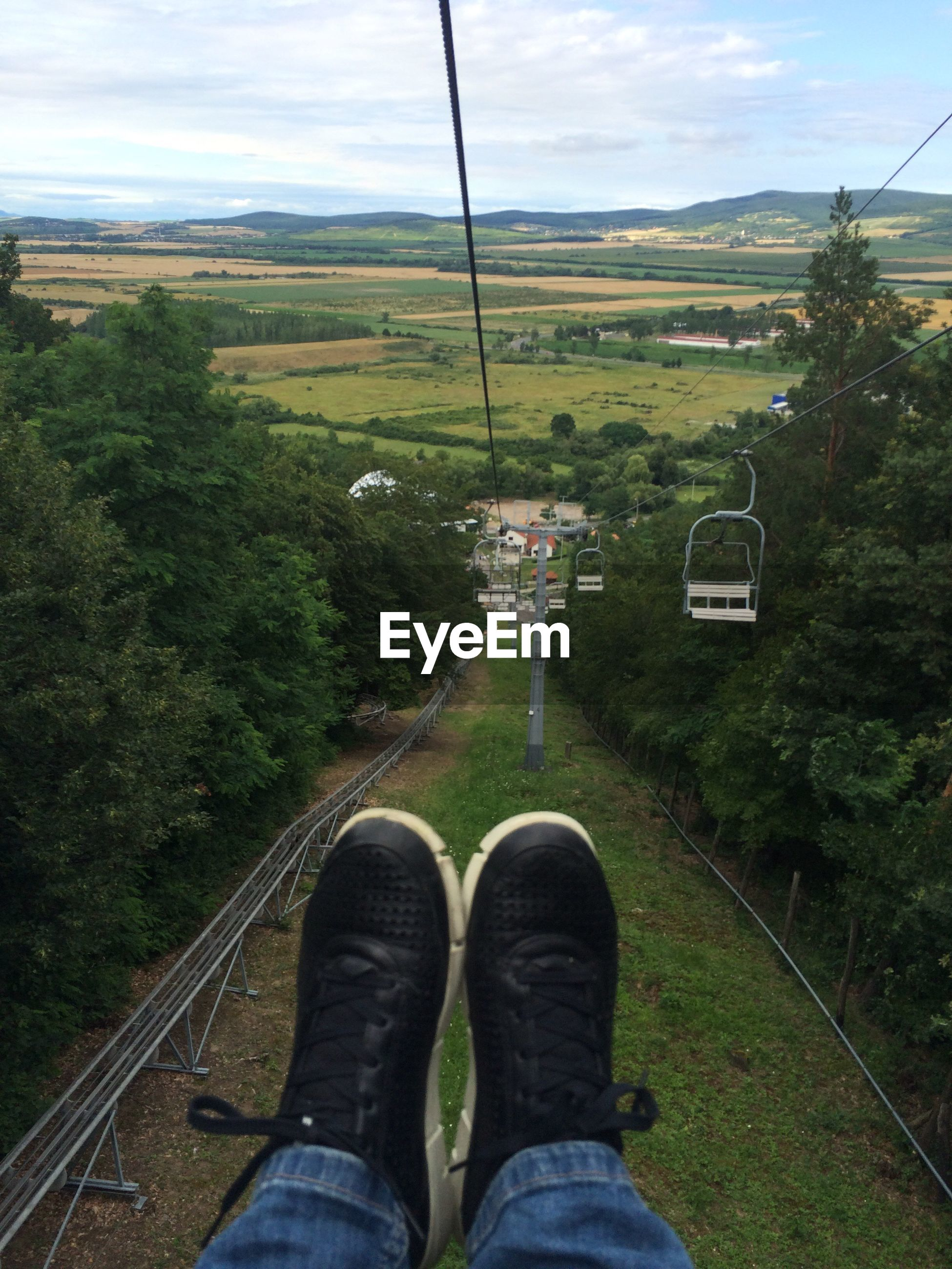 Low section of person on overhead cable car against sky