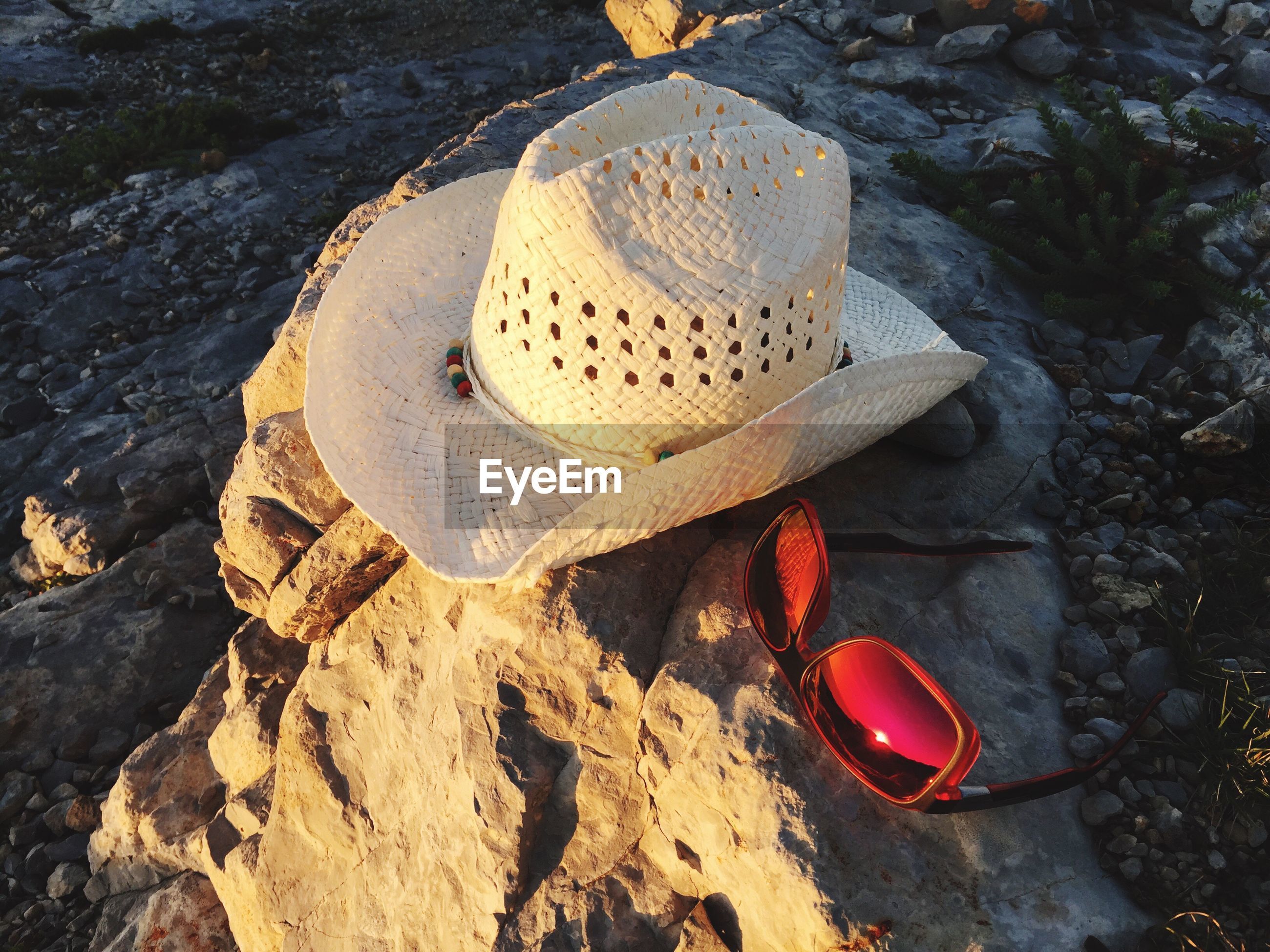 High angle view of sunhat and sunglasses on rock