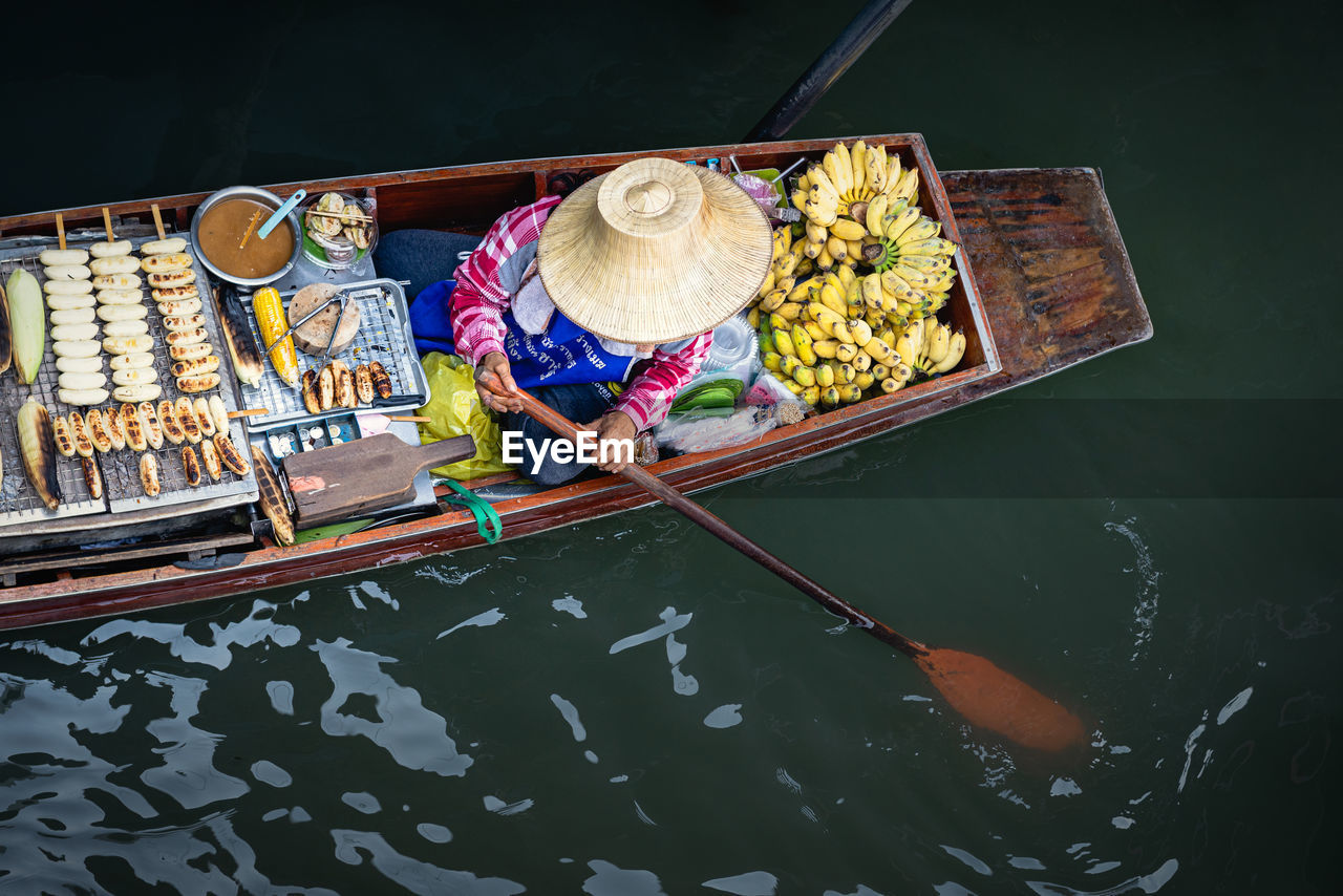 High angle view of man selling food in boat on river