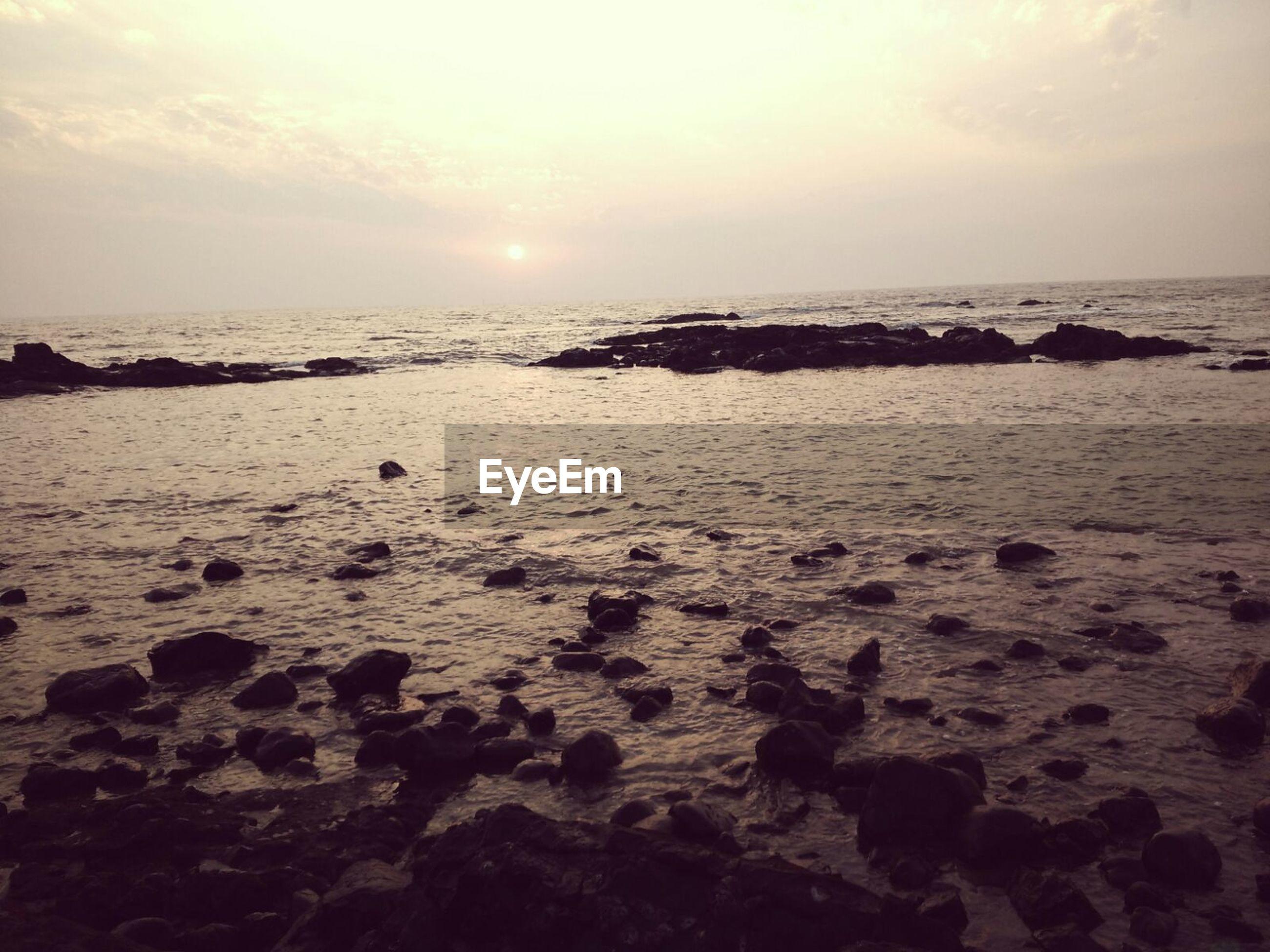 sea, horizon over water, beach, water, scenics, tranquil scene, shore, tranquility, sunset, beauty in nature, sky, nature, sun, idyllic, rock - object, wave, sand, sunlight, coastline, remote