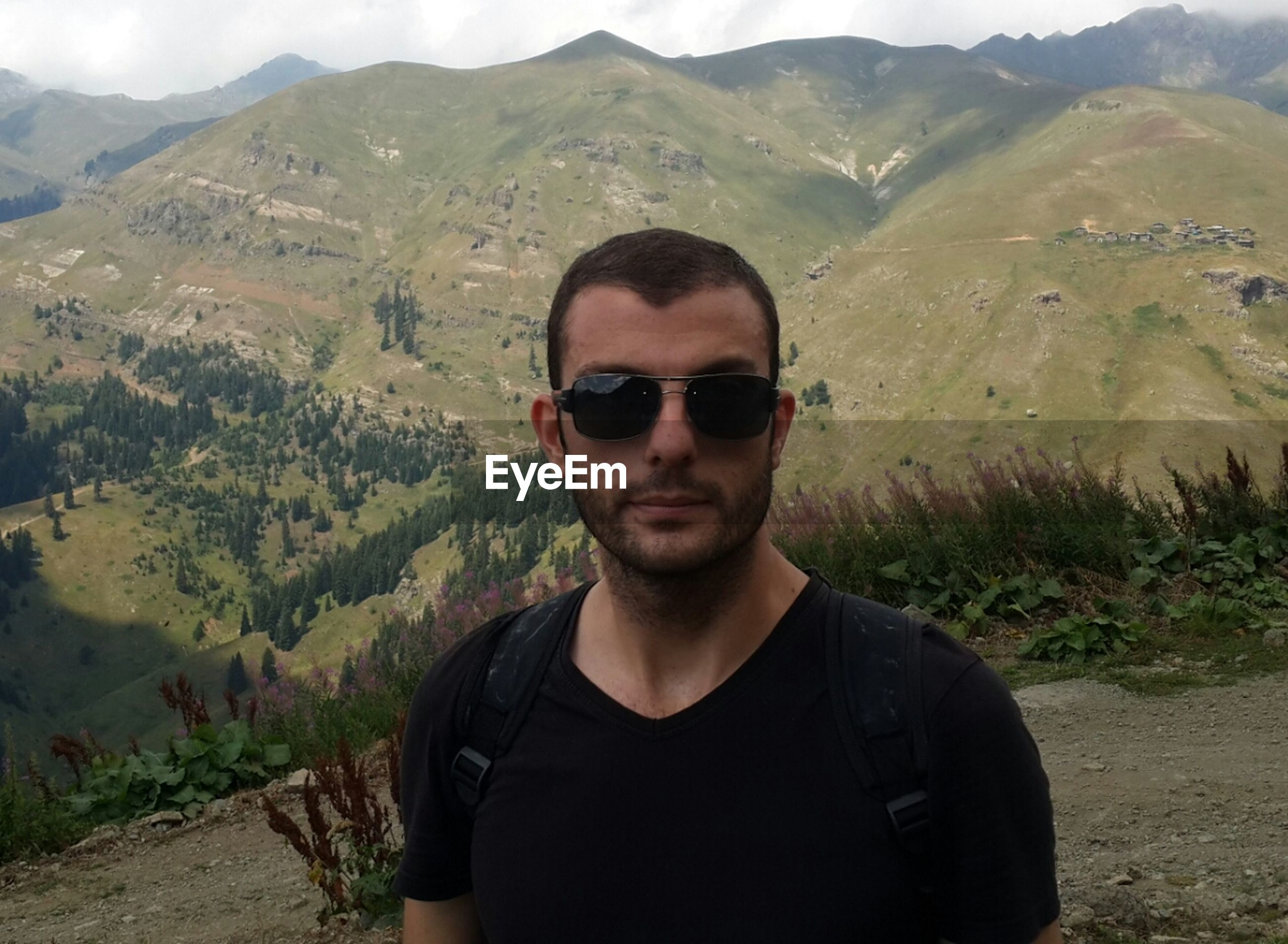 mountain, young adult, portrait, lifestyles, looking at camera, young men, person, leisure activity, casual clothing, mountain range, landscape, front view, sunglasses, tranquility, smiling, scenics, beauty in nature, nature