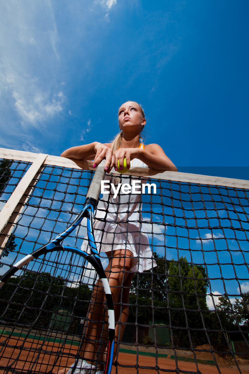 one person, sport, low angle view, sky, front view, nature, real people, lifestyles, full length, day, tennis, tennis racket, leisure activity, young adult, athlete, clothing, net - sports equipment, blue, outdoors