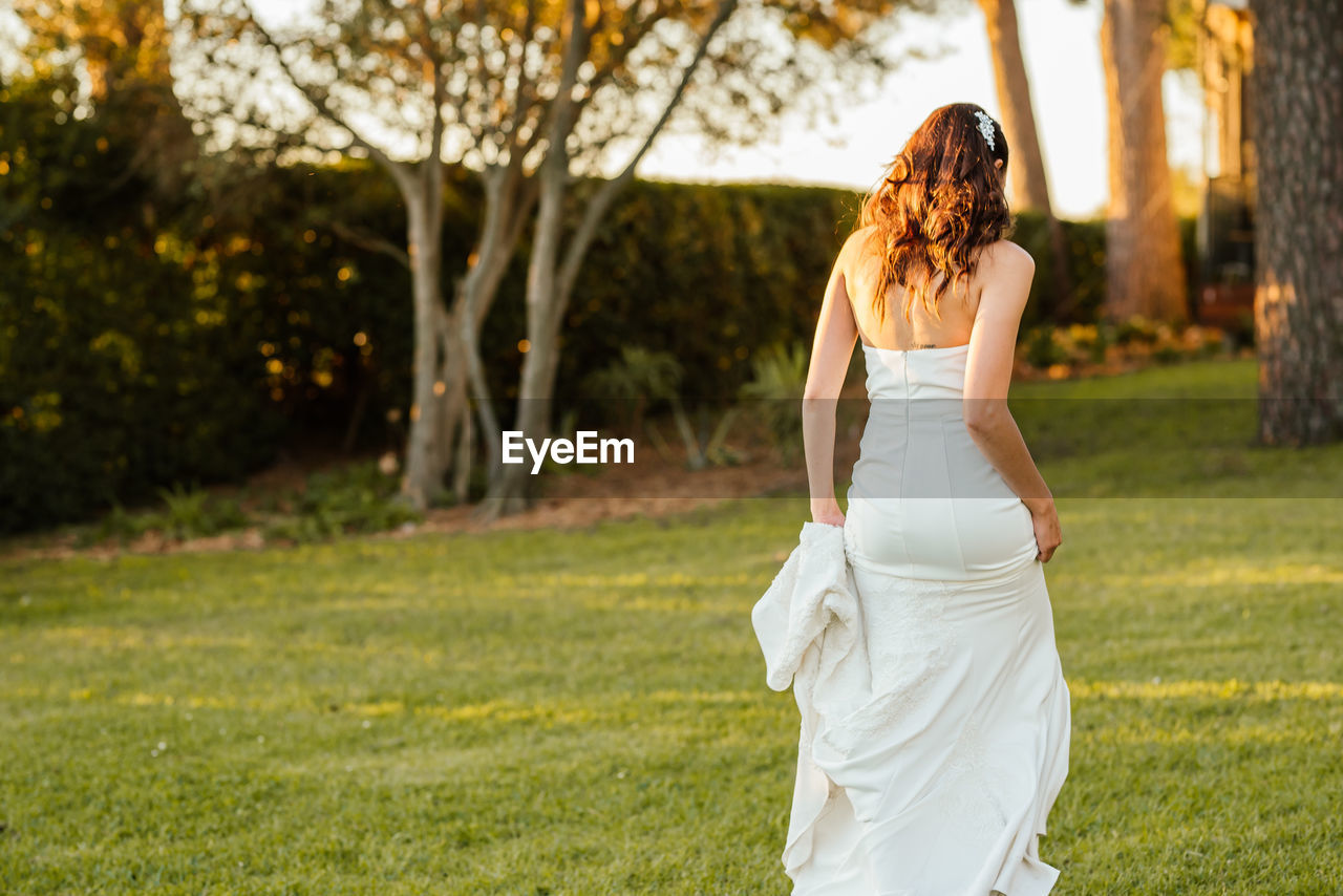 REAR VIEW OF WOMAN IN WHITE FIELD