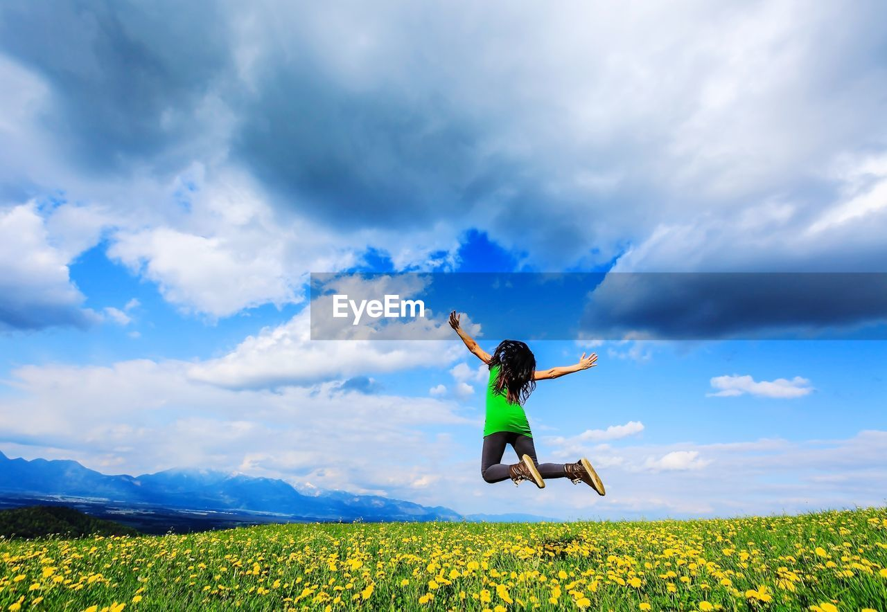 Woman Jumping On Field Against Sky