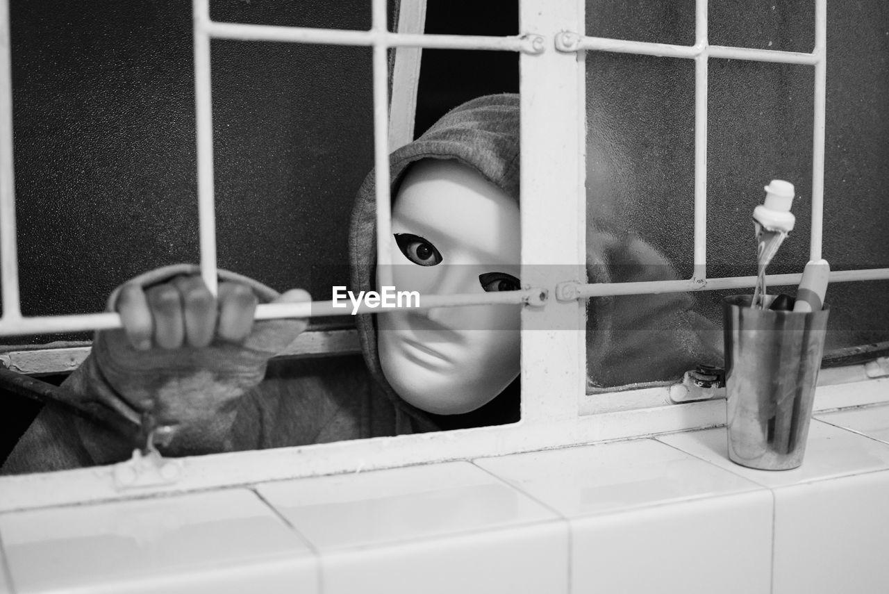 Close-Up Portrait Of Burglar Wearing Mask Peeking Through Window