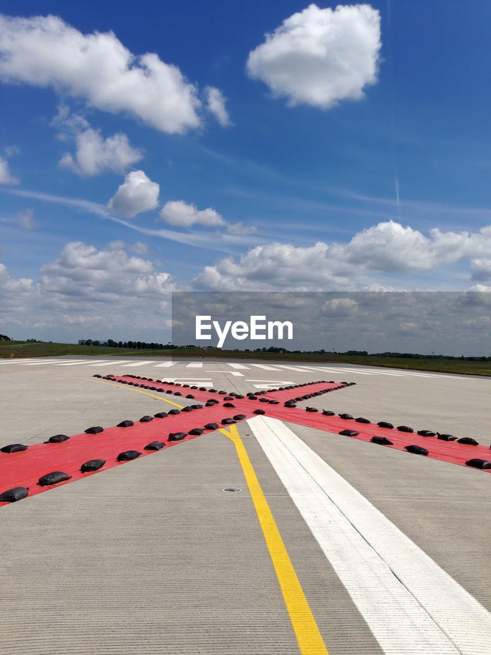 Cross Shape On Airport Runway Against Sky