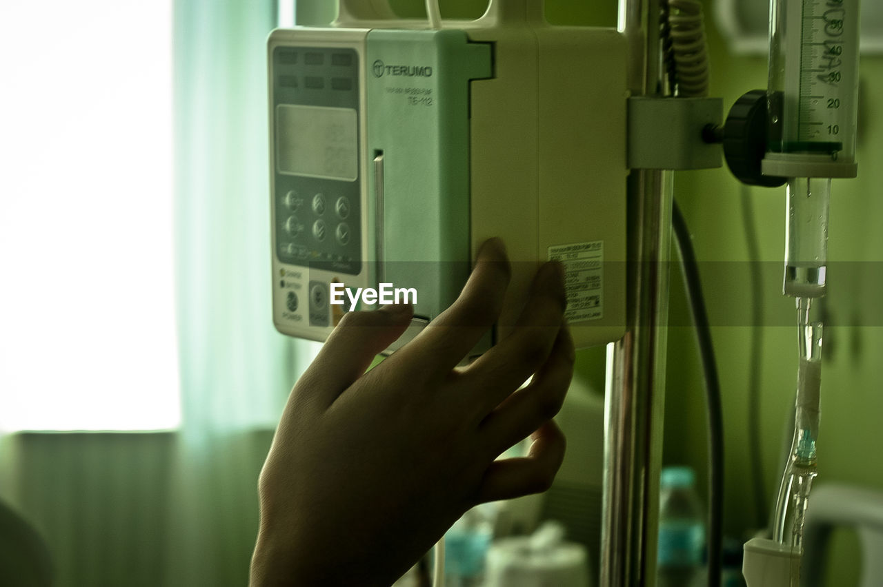 Cropped image of hand on machinery at hospital