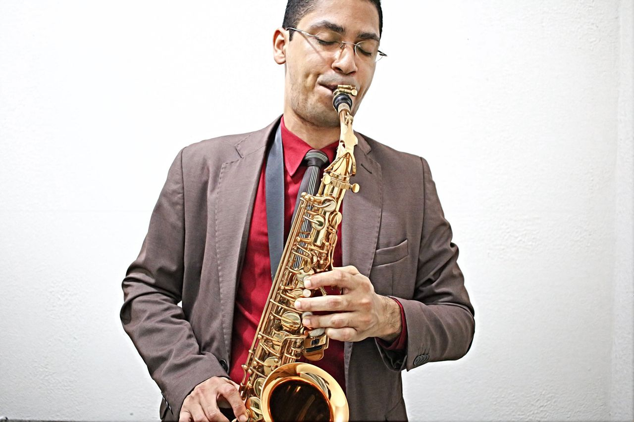 Man playing saxophone while standing against white wall