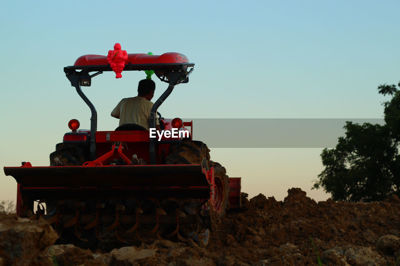 Rear View Of Man In Tractor Ploughing Field Against Sky