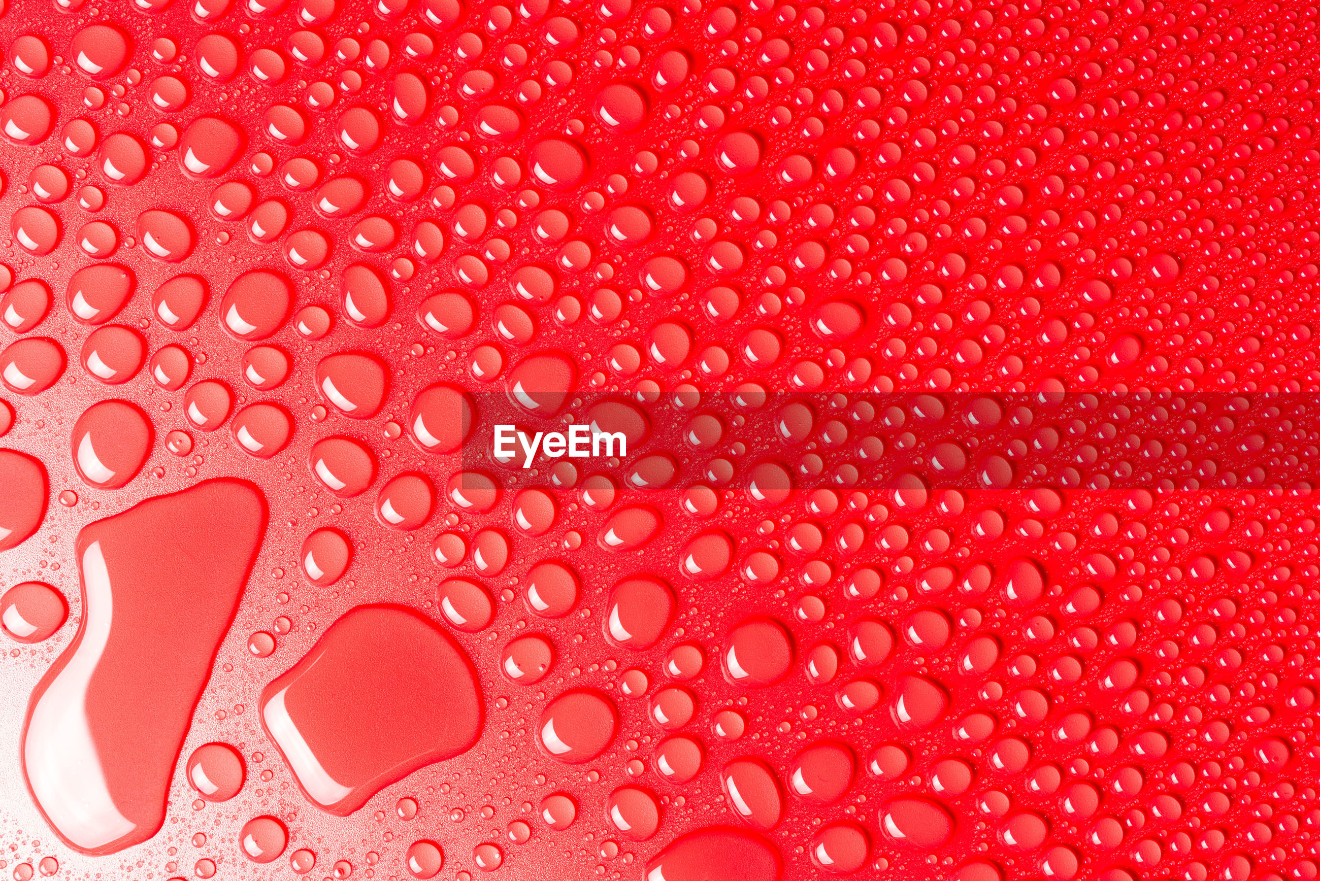 Droplets of water on a red, matte background illuminated with a delicate light.