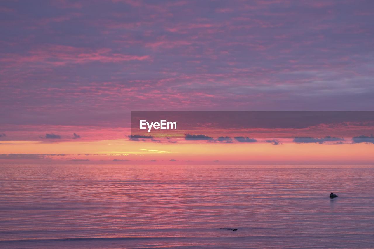 Scenic view of sea against orange sky