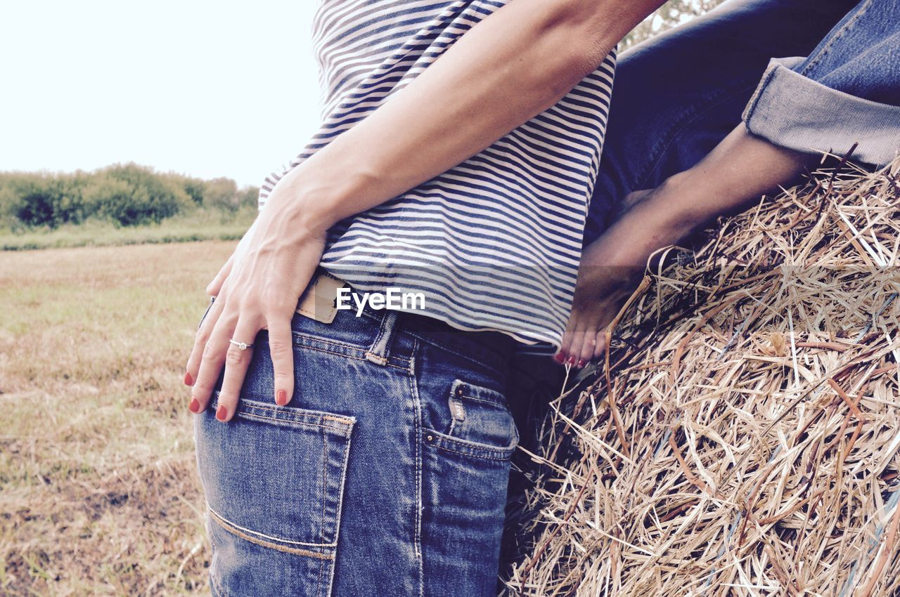 Midsection of couple embracing by hay at field