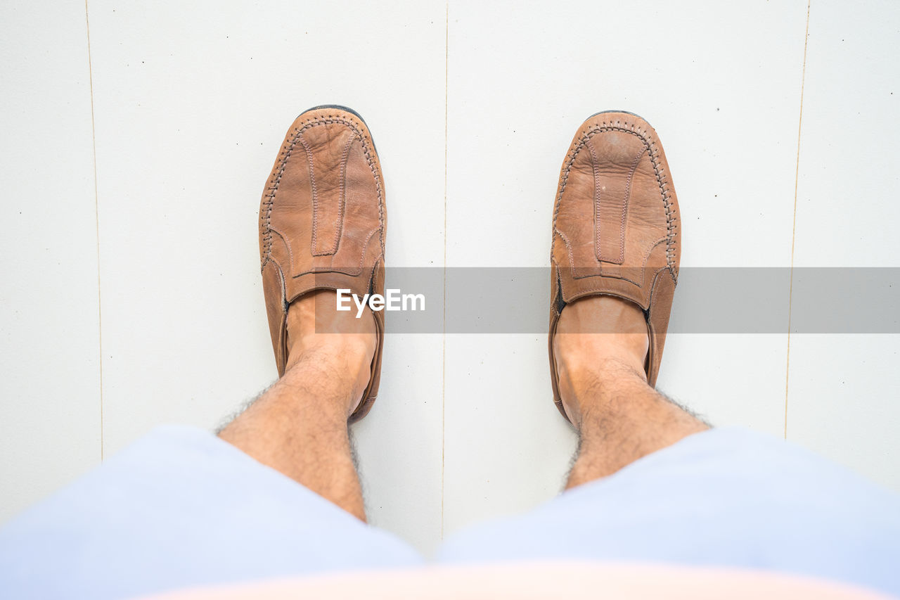 Low section of man wearing brown shoes while standing on floor
