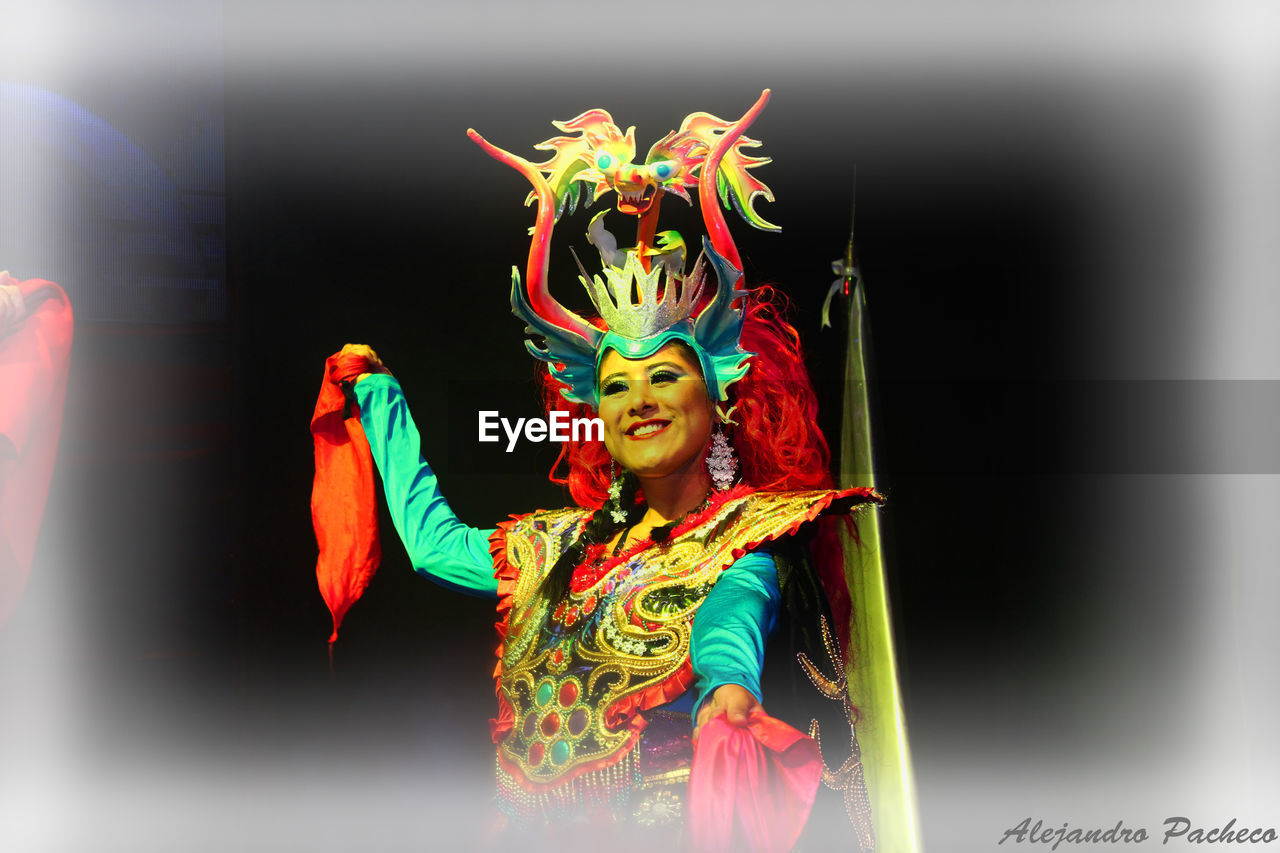 performance, cultures, costume, traditional clothing, front view, arts culture and entertainment, multi colored, standing, celebration, one person, traditional festival, looking at camera, performing arts event, traditional dancing, outdoors, real people, smiling, day, stage costume, chinese dragon, clown, people