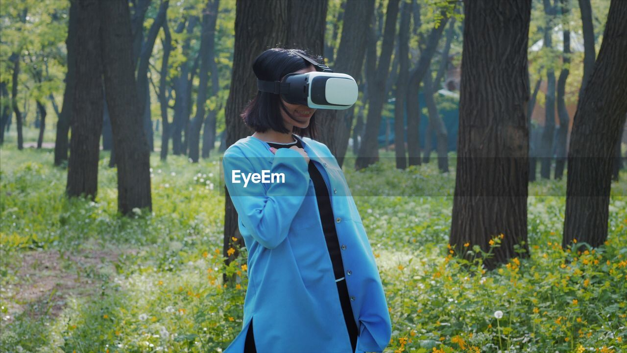 Woman wearing virtual reality simulator while standing on field at forest