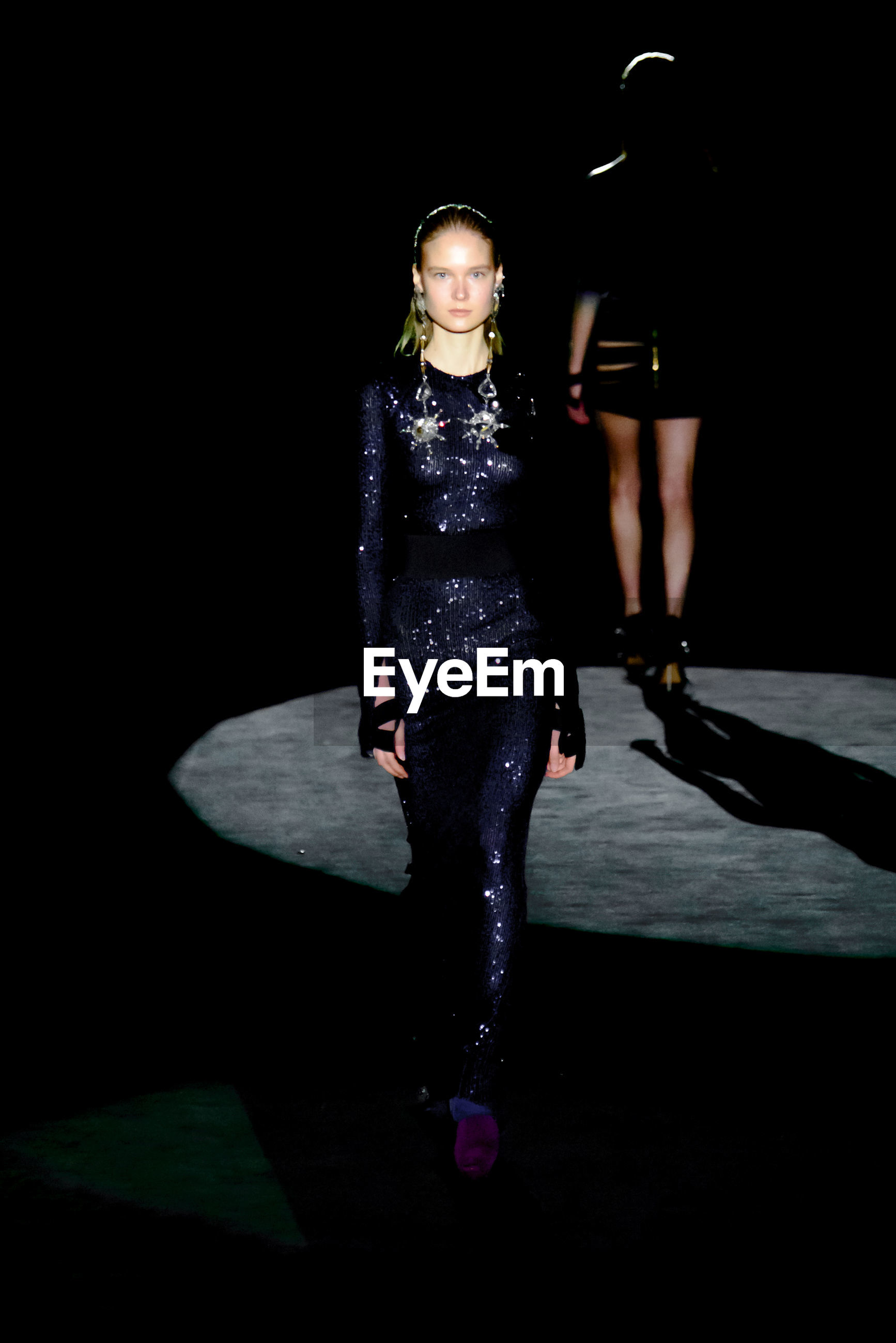 full length, one person, adult, women, fashion, portrait, young adult, black, clothing, indoors, black background, shadow, performance art, looking at camera, darkness, footwear, studio shot, front view, standing, night, arts culture and entertainment, person, runway, female, dress