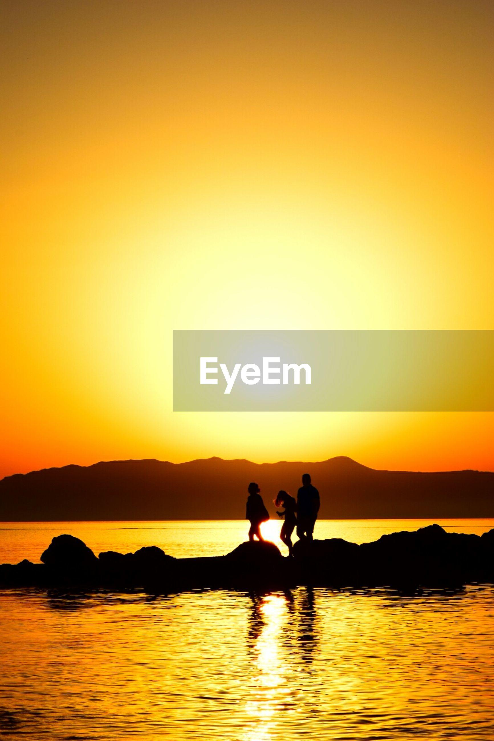 Silhouette people enjoying on rocks in sea water of crete during sunset