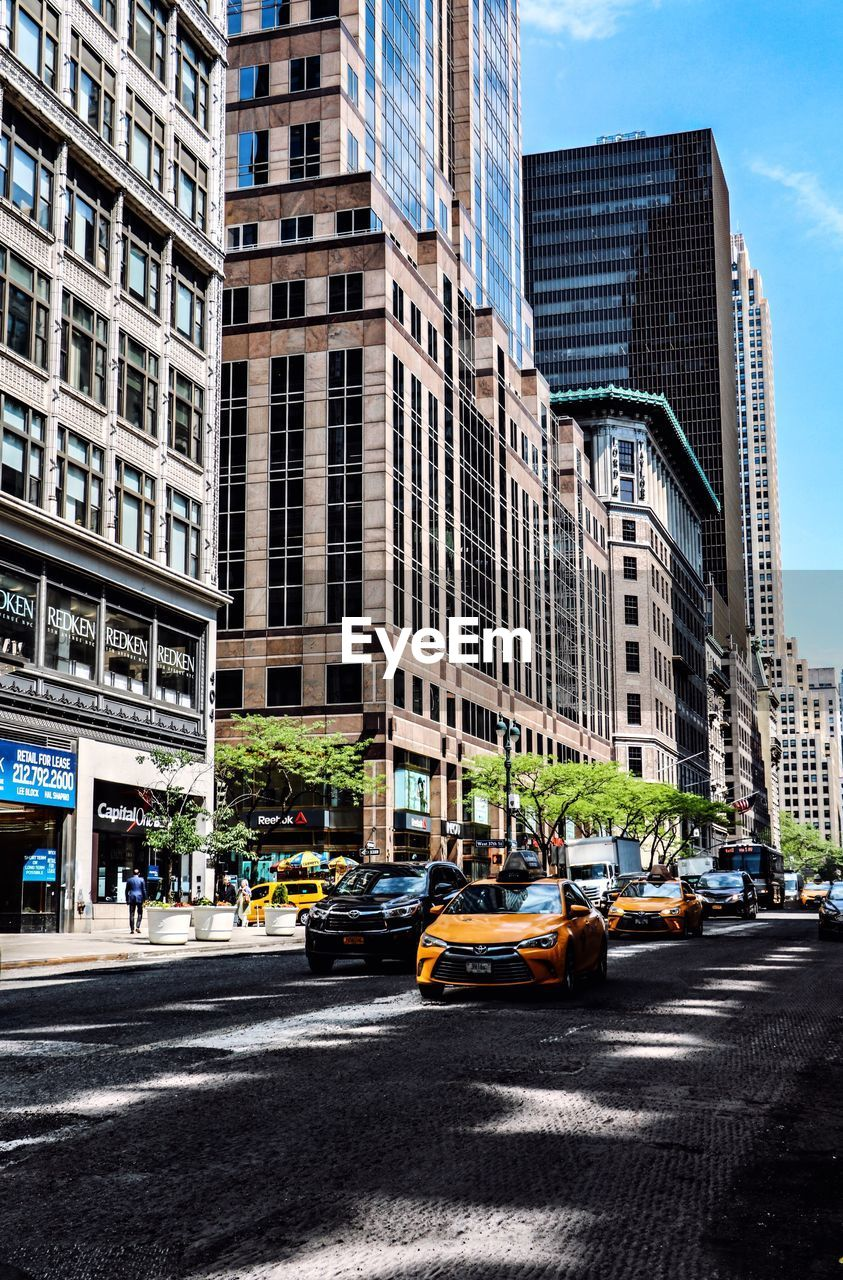 city, architecture, building exterior, motor vehicle, street, car, mode of transportation, transportation, built structure, road, city life, building, office building exterior, taxi, skyscraper, city street, yellow taxi, travel destinations, day, on the move, modern, outdoors, cityscape, light