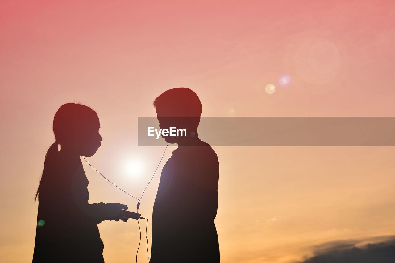 Silhouette Friends Listening Music Through Headphones Against Sky During Sunset