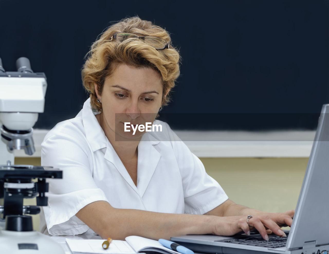 Scientist using laptop at laboratory
