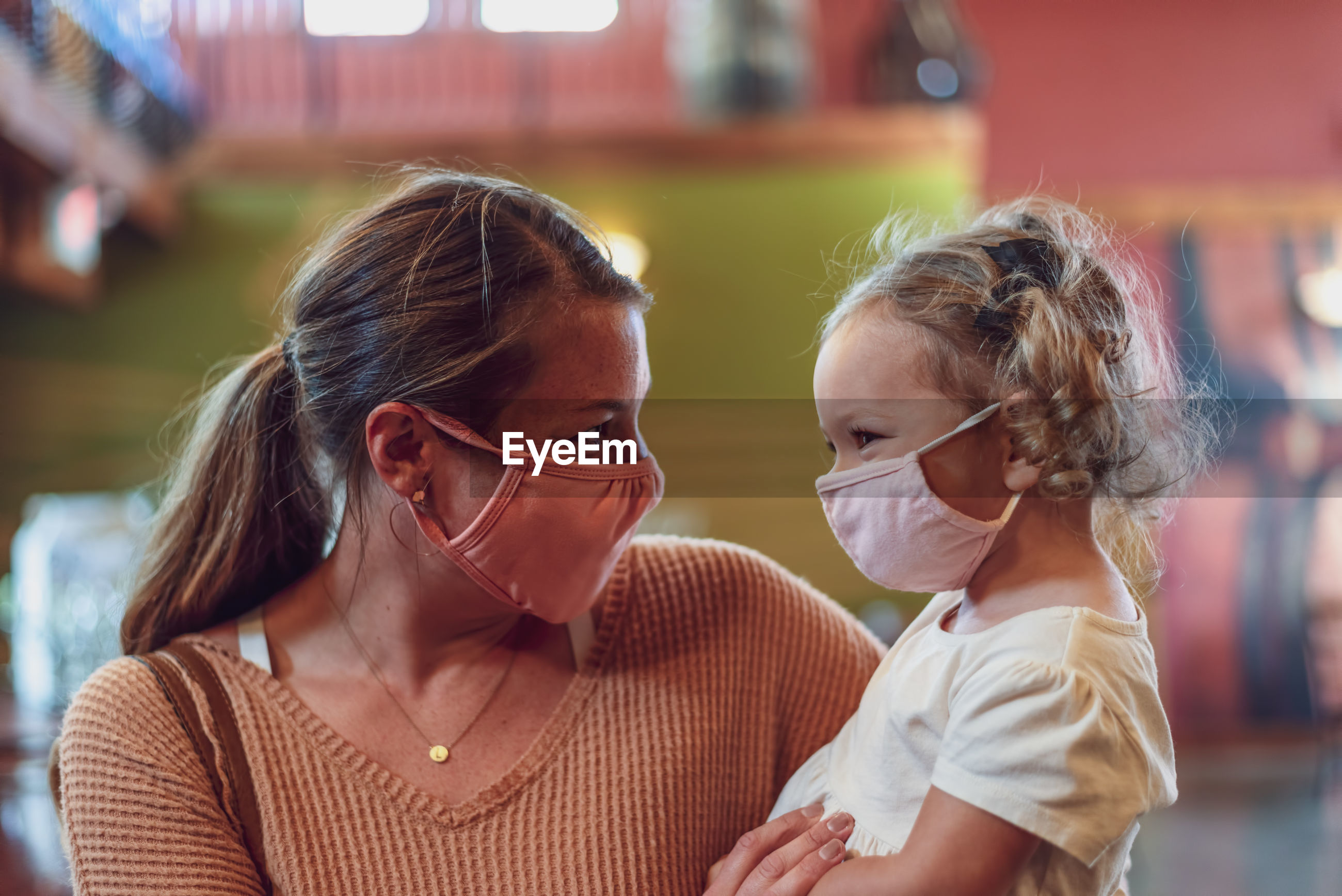 Close-up of mother and daughter wearing mask sanding outdoors
