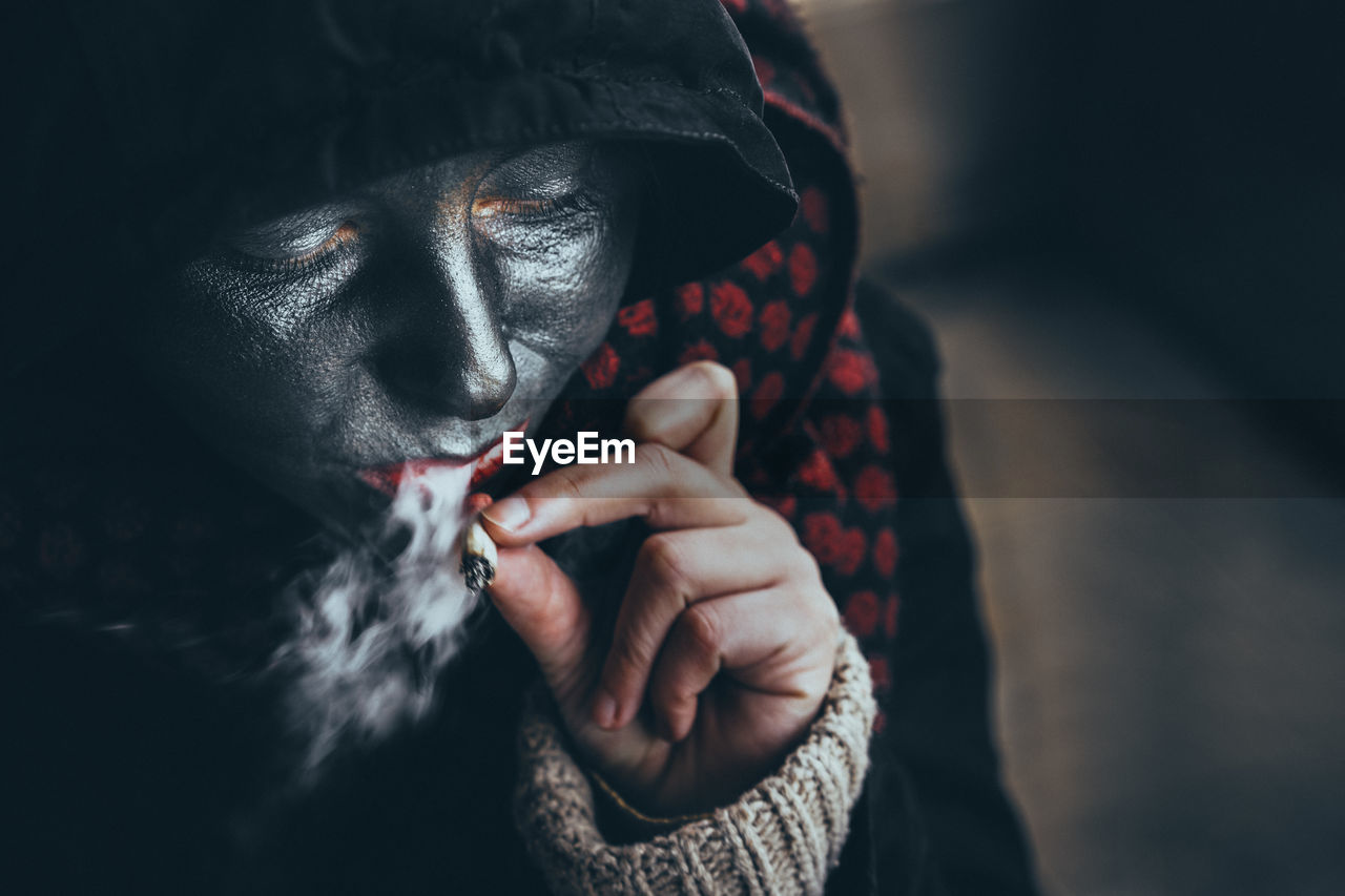 Close-Up Of Woman With Face Paint Smoking Cigarette