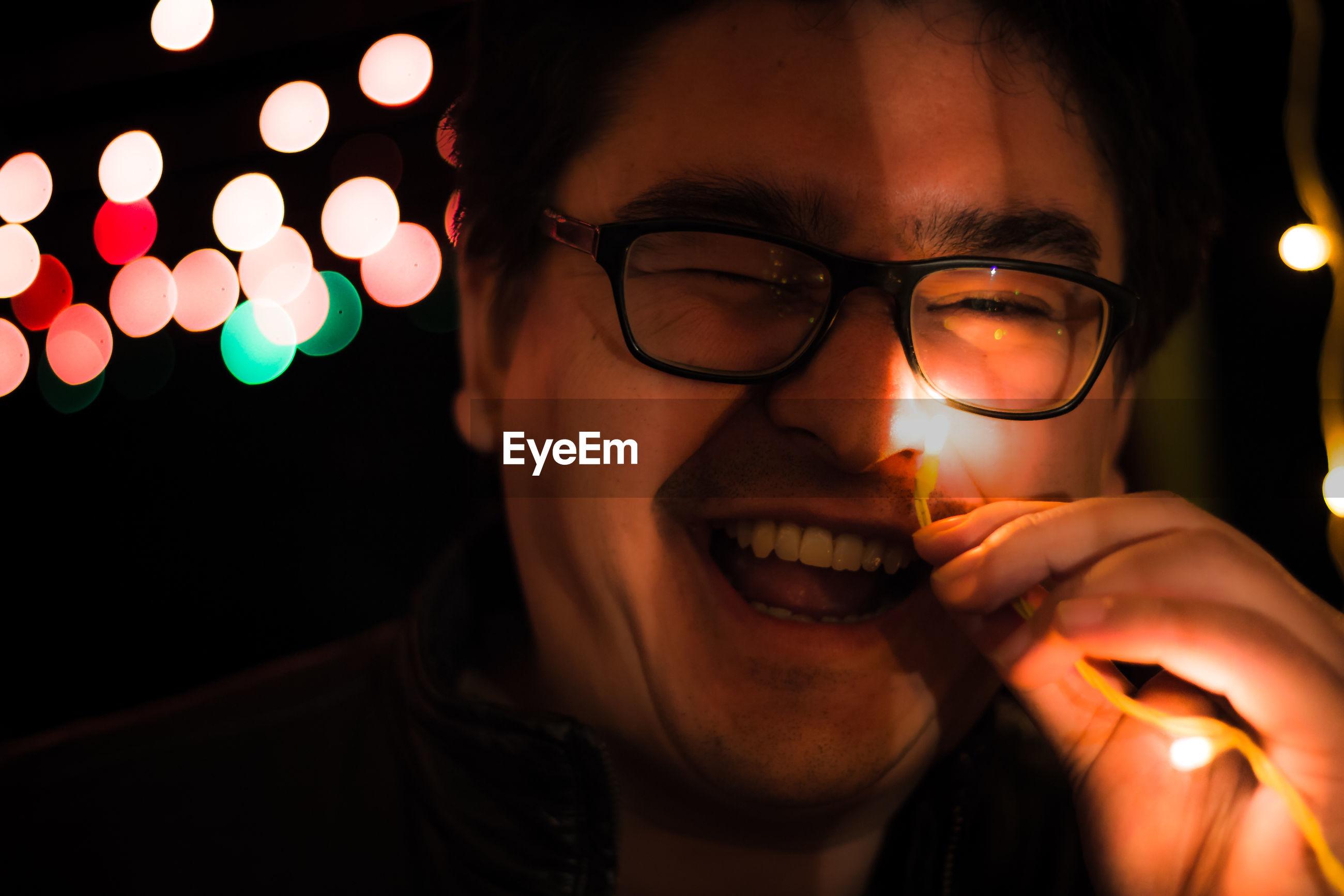 Close-up of happy young man holding illuminated light