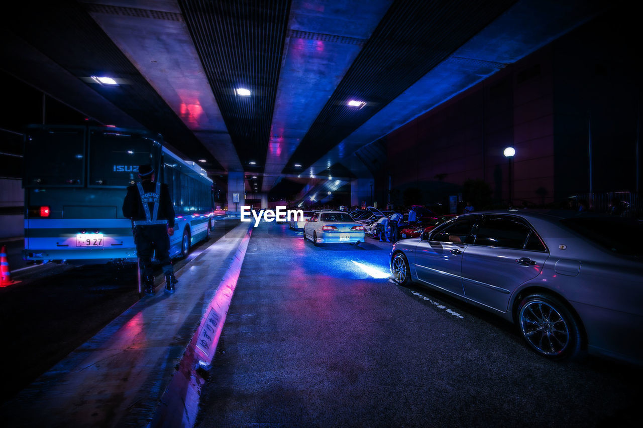 car, motor vehicle, illuminated, mode of transportation, transportation, land vehicle, night, city, architecture, street, road, built structure, lighting equipment, motion, building exterior, no people, parking, parking lot, outdoors, the way forward, nightlife, garage
