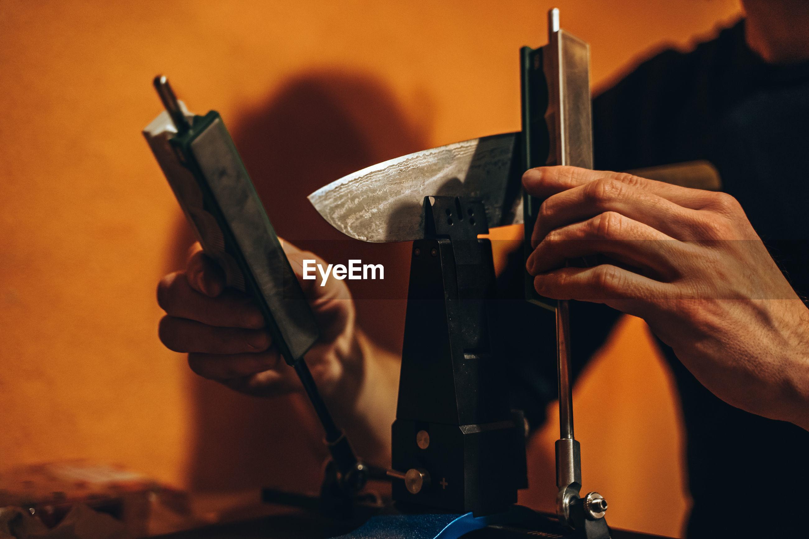 Cropped hands of manual worker repairing machinery in workshop