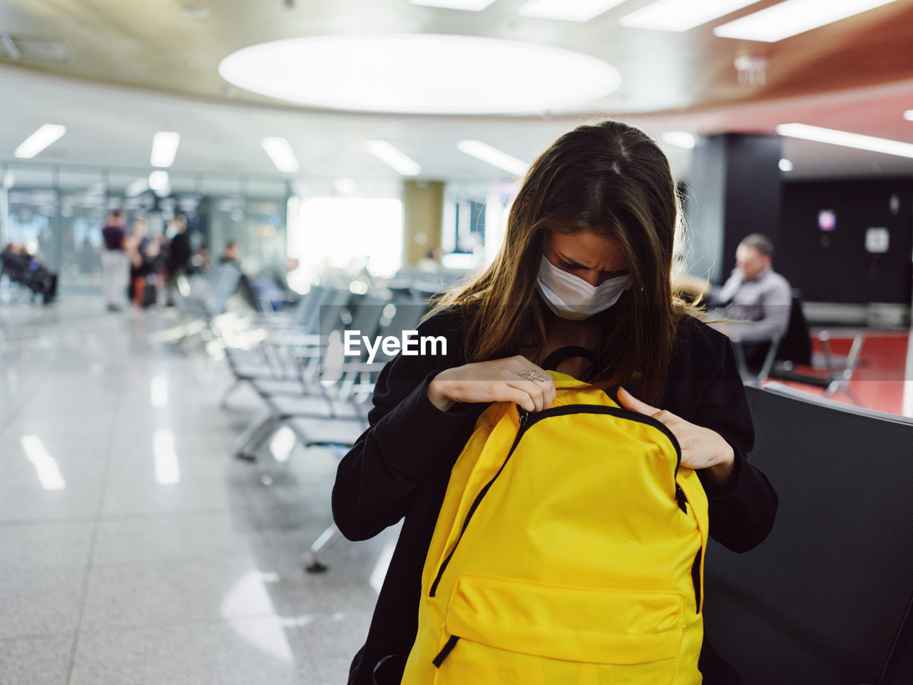 WOMAN STANDING IN AIRPORT